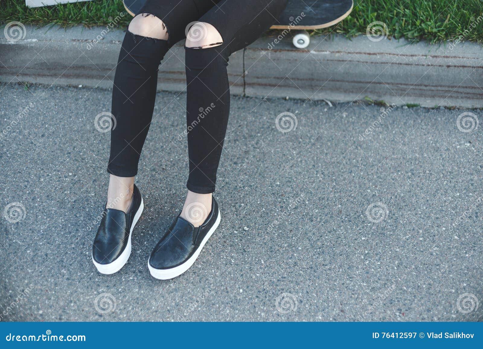 Jeune femme dans des jeans, espadrilles se reposant au sol à côté de sa planche à roulettes dehors