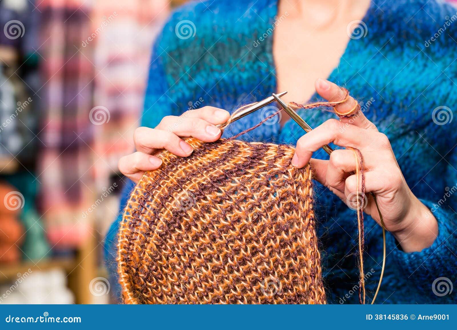 Jeune femme dans la boutique de tricotage avec l aiguille circulaire