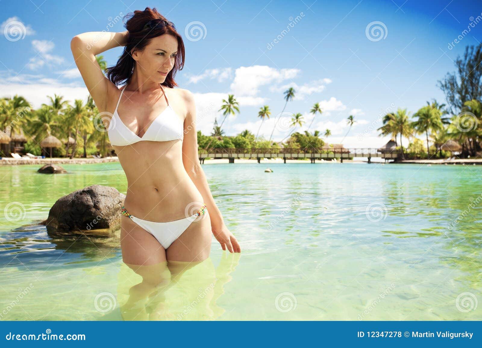 Jeune femme dans le bikini blanc restant à côté de la plage