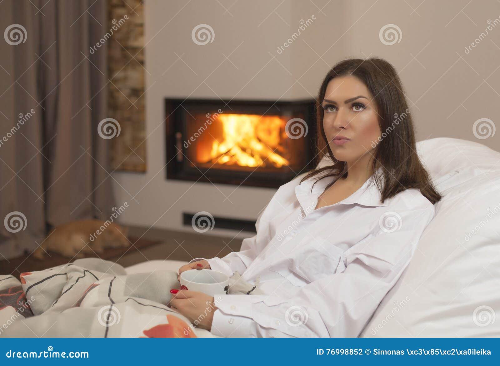 Jeune femme dans le lit buvant le chat et la cheminée chauds de sommeil de thé