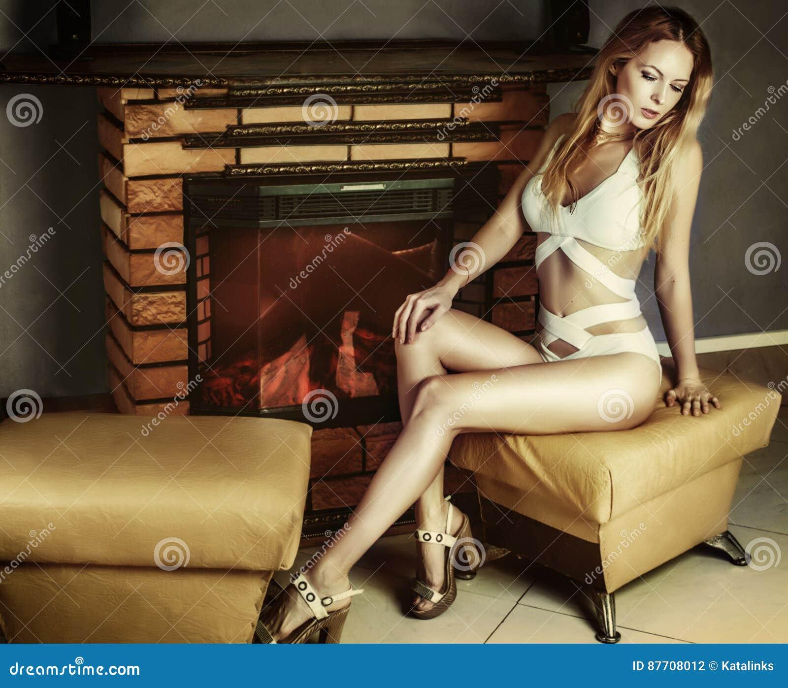 Jeune femme dans le maillot de bain sur les talons se reposant près de la cheminée