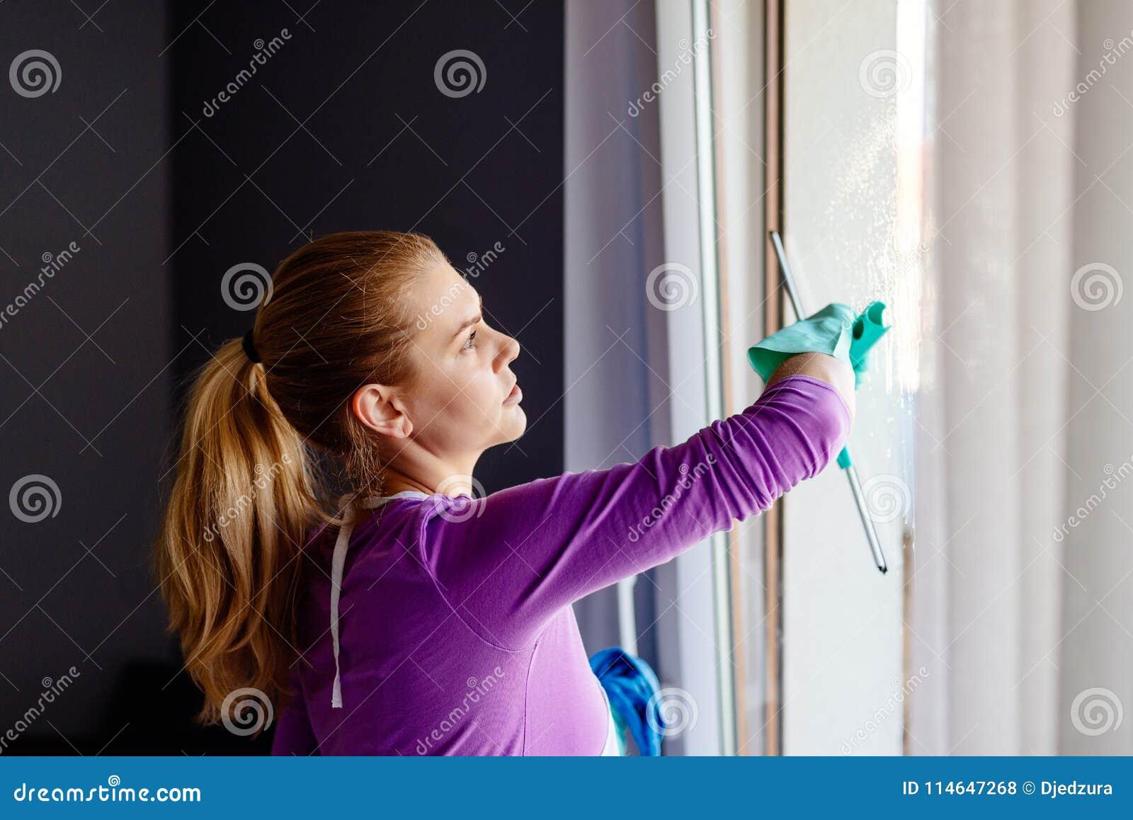 Jeune femme dans les fenêtres blanches de nettoyage de tablier