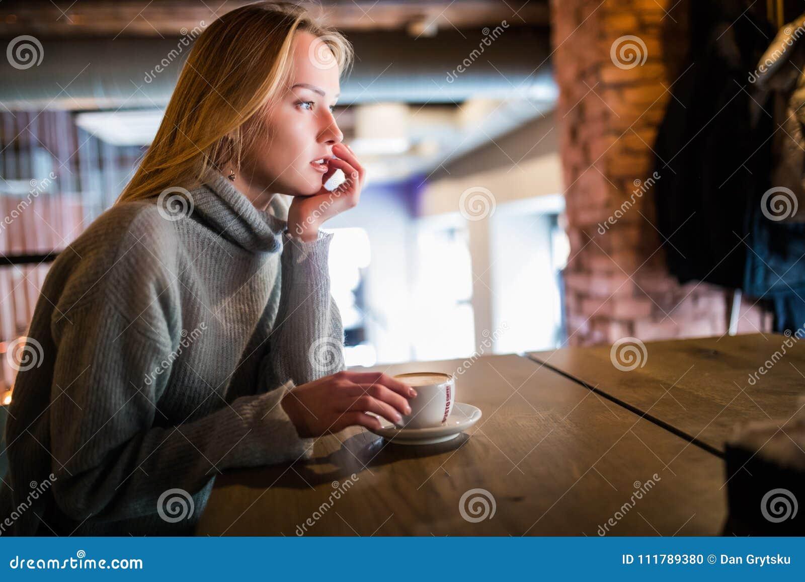 Jeune femme de beauté dans un café potable de café