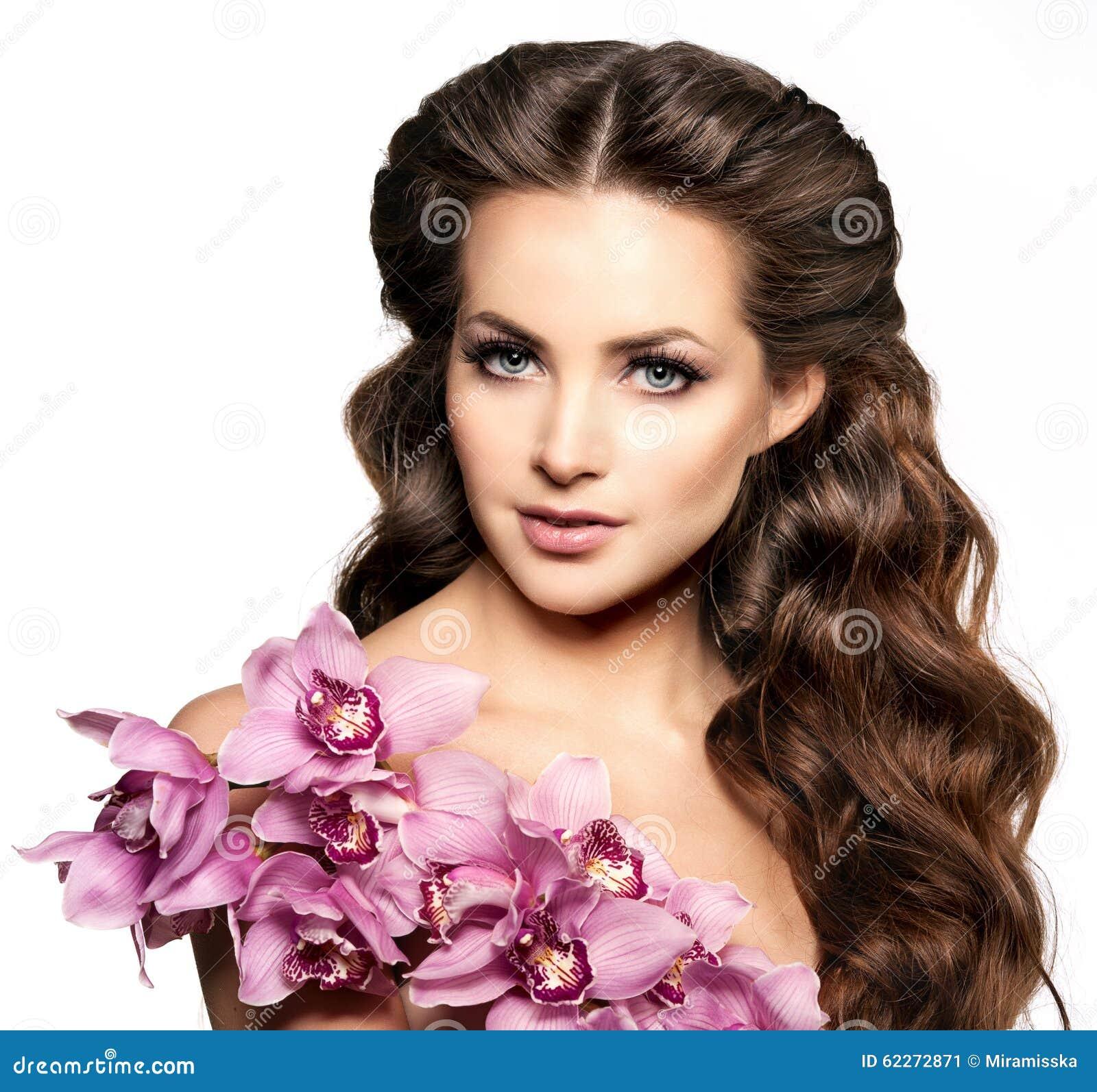 Jeune femme de beauté, longs cheveux bouclés de luxe avec la fleur d orchidée H