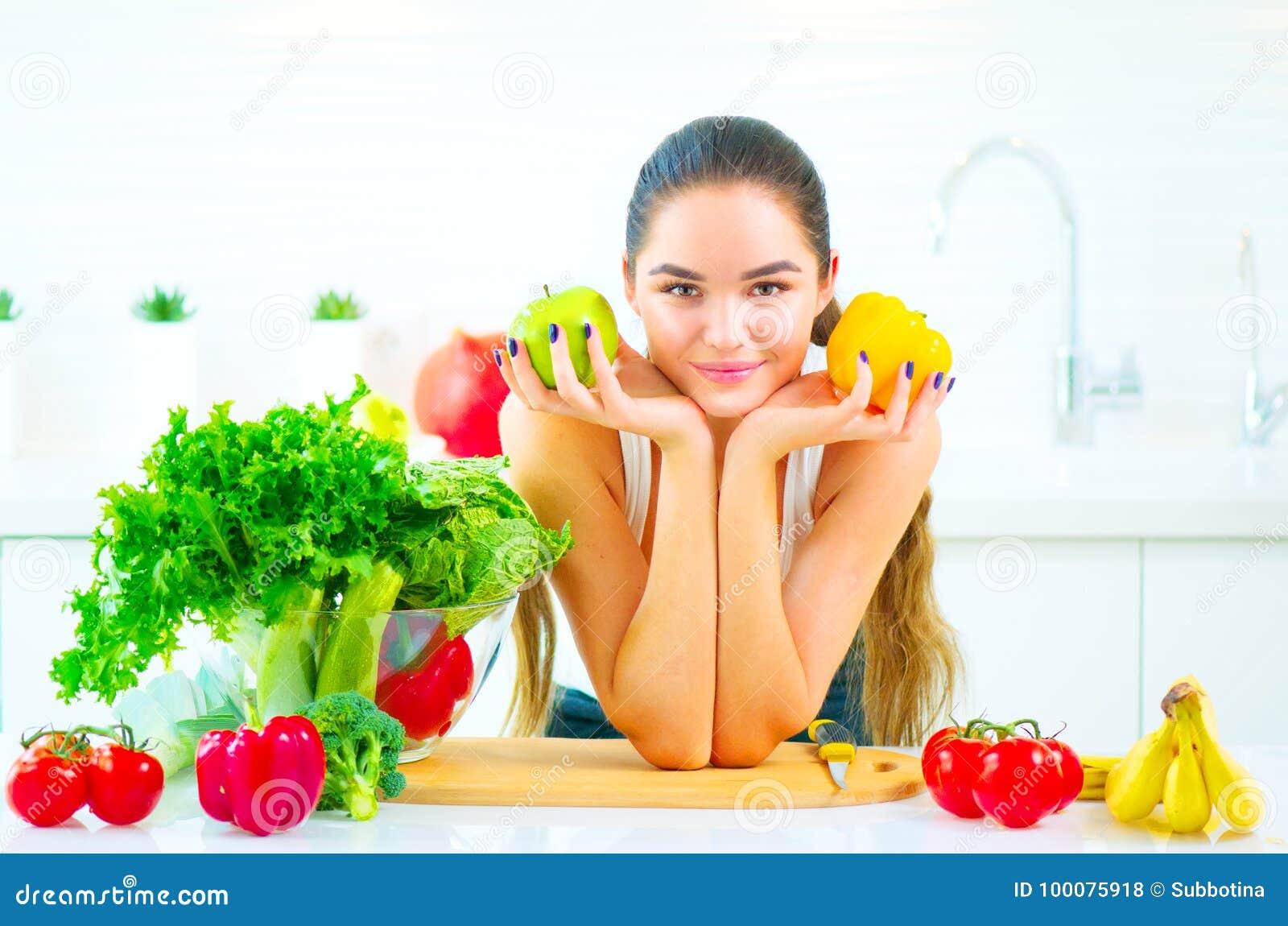Jeune femme de beauté tenant les légumes frais et les fruits dans sa cuisine à la maison