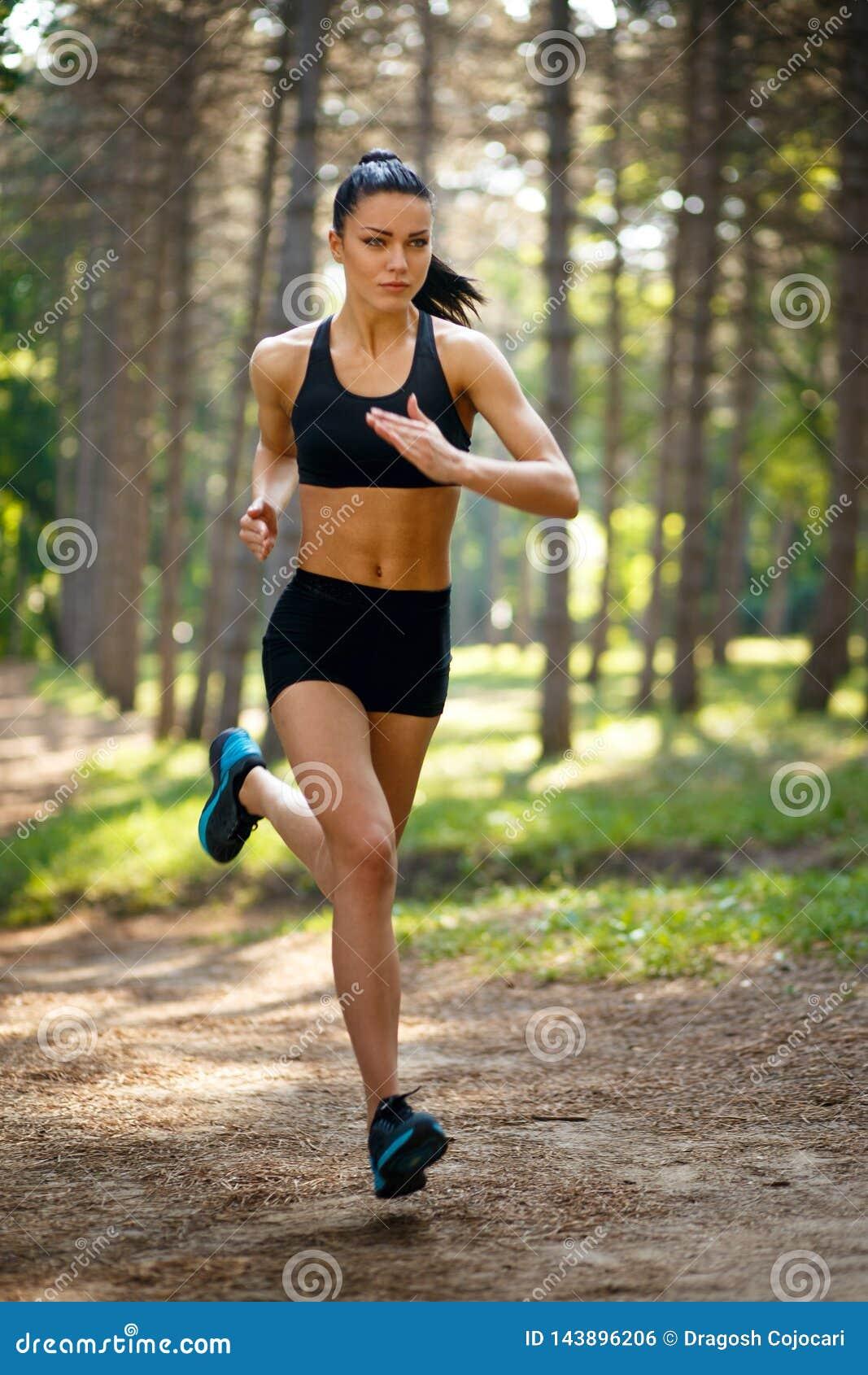 Jeune femme de brune courant en parc, corps convenable en bonne santé et parfait de ton Séance d entraînement dehors Concept de m