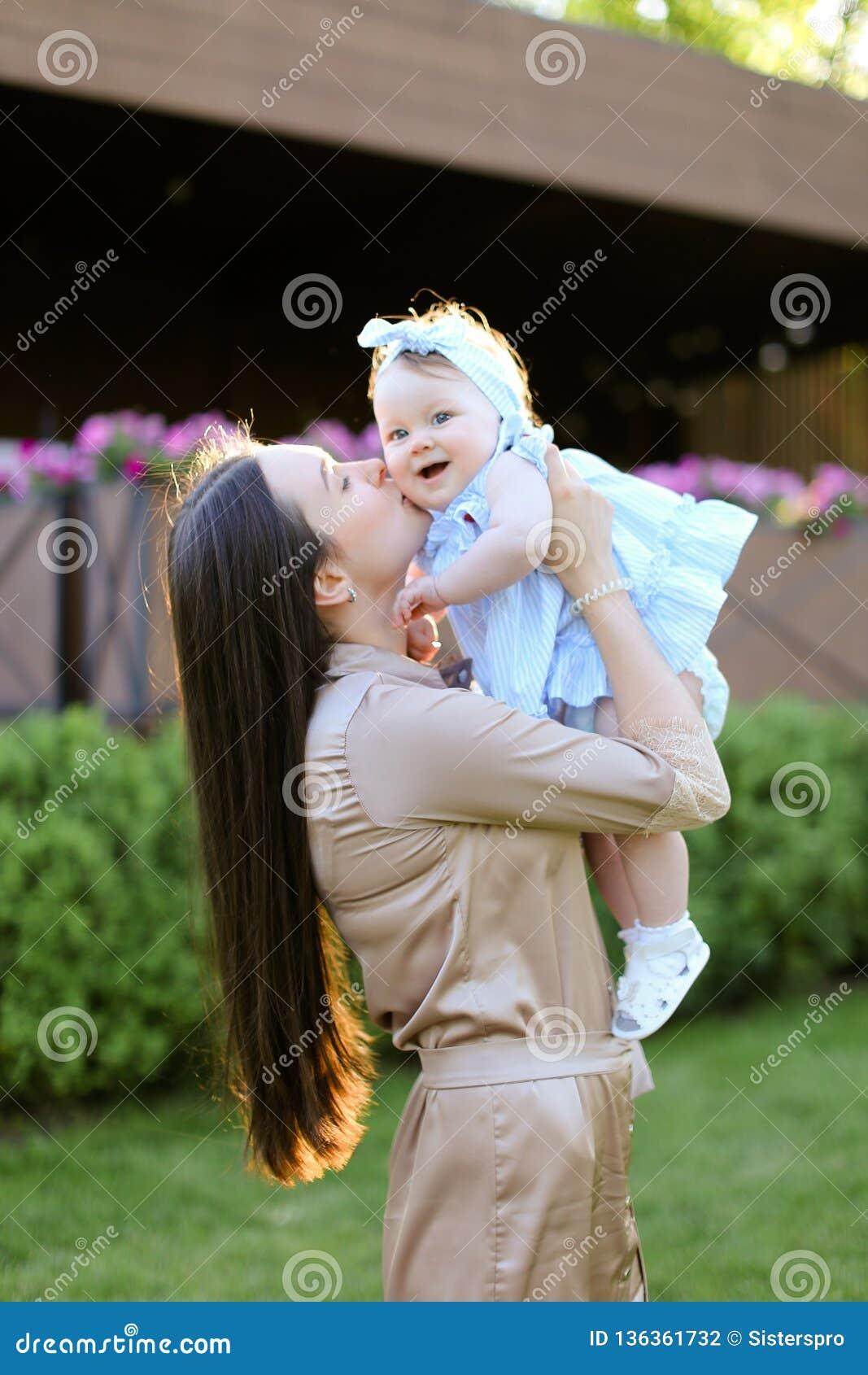 Jeune femme de brune tenant et embrassant peu de fille