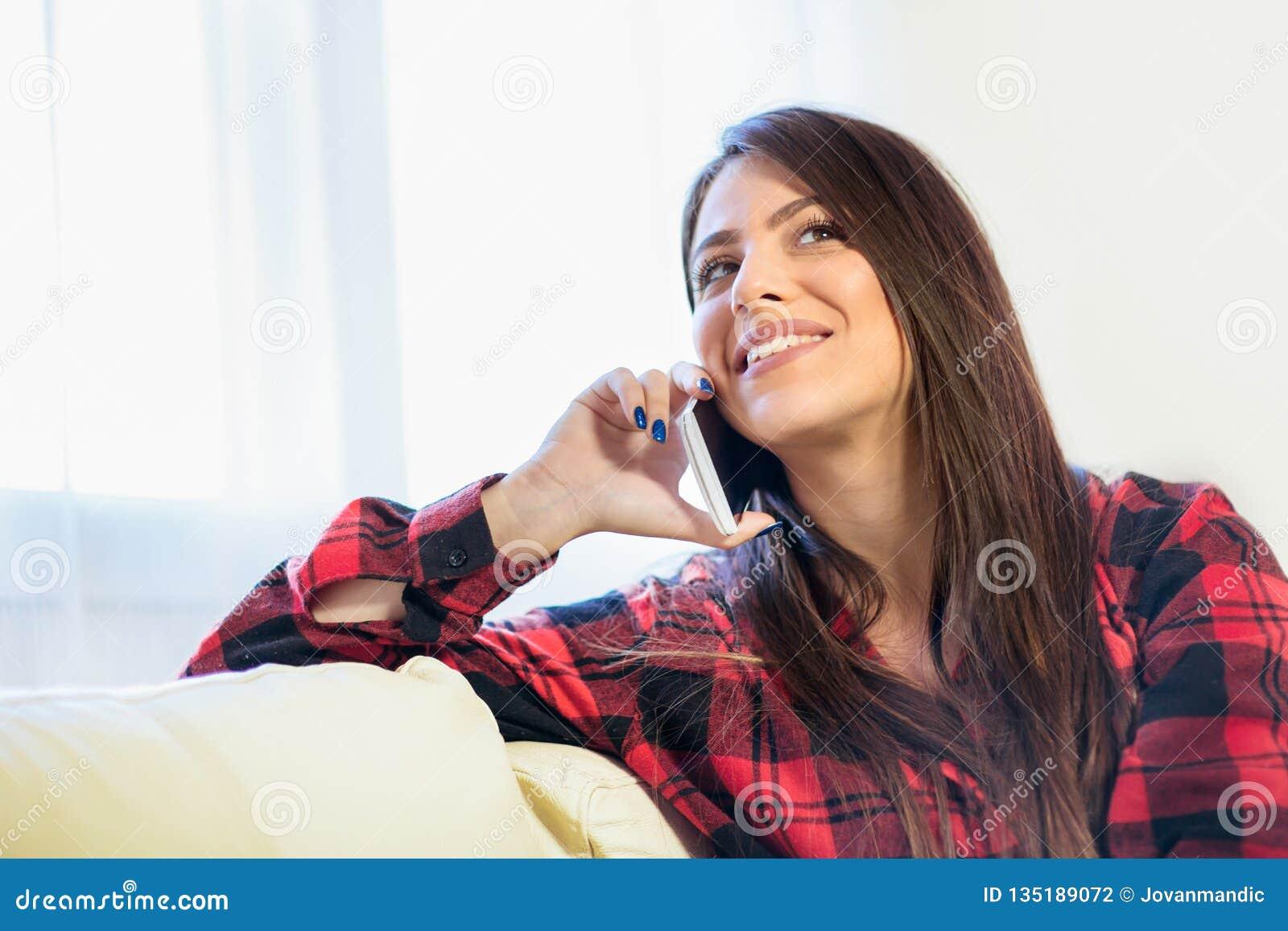 Jeune femme de charme appréciant une conversation à son téléphone portable tout en se reposant sur le sofa à la maison