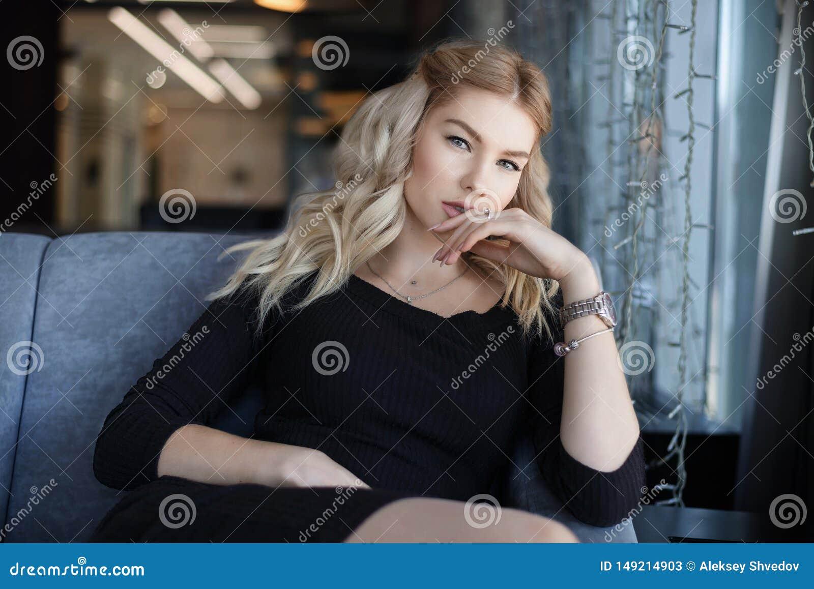 Jeune femme de charme de portrait avec le sourire amical, long sourire de cheveux blonds