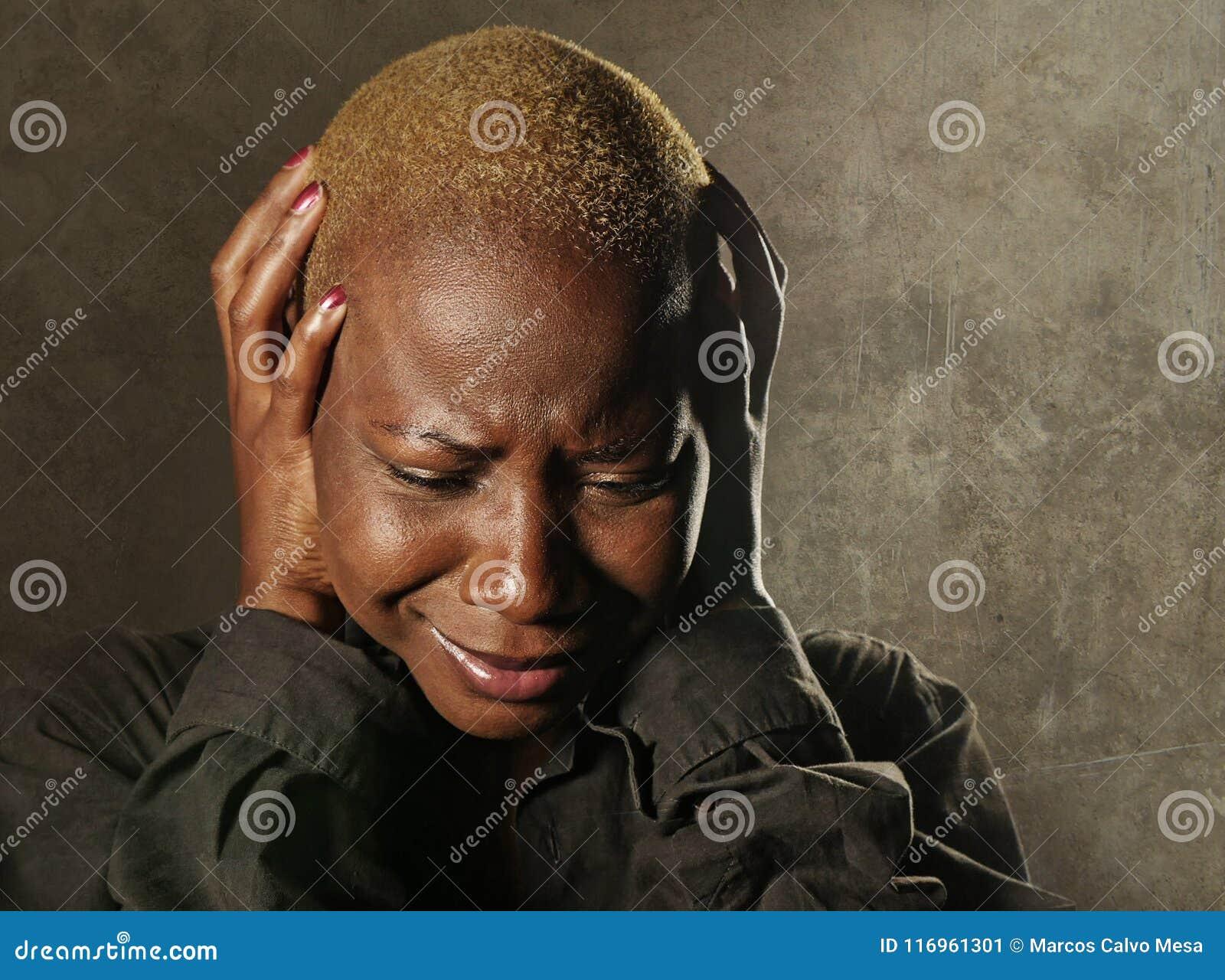 Jeune femme de couleur afro-américaine triste et déprimée élégante pleurant de désespoir jugeant principal avec les mains se sent