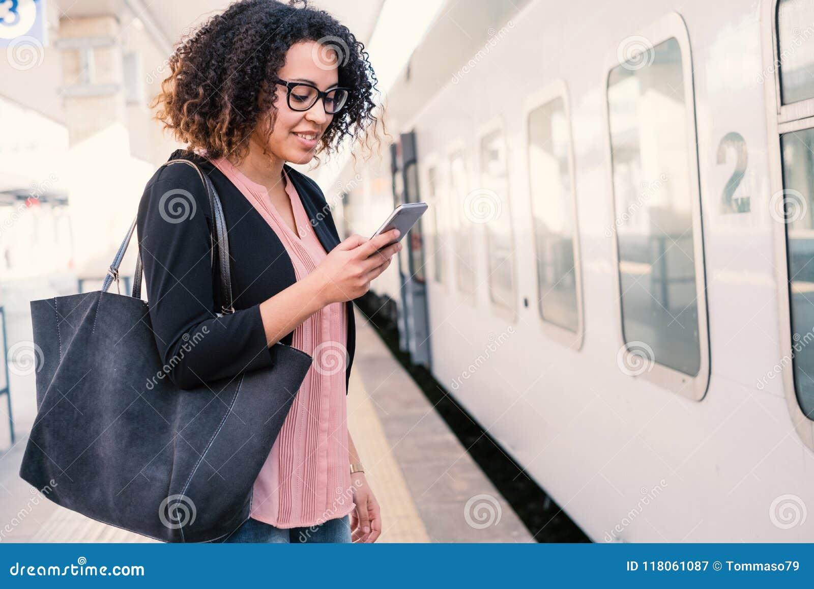 Jeune femme de couleur attendant le train