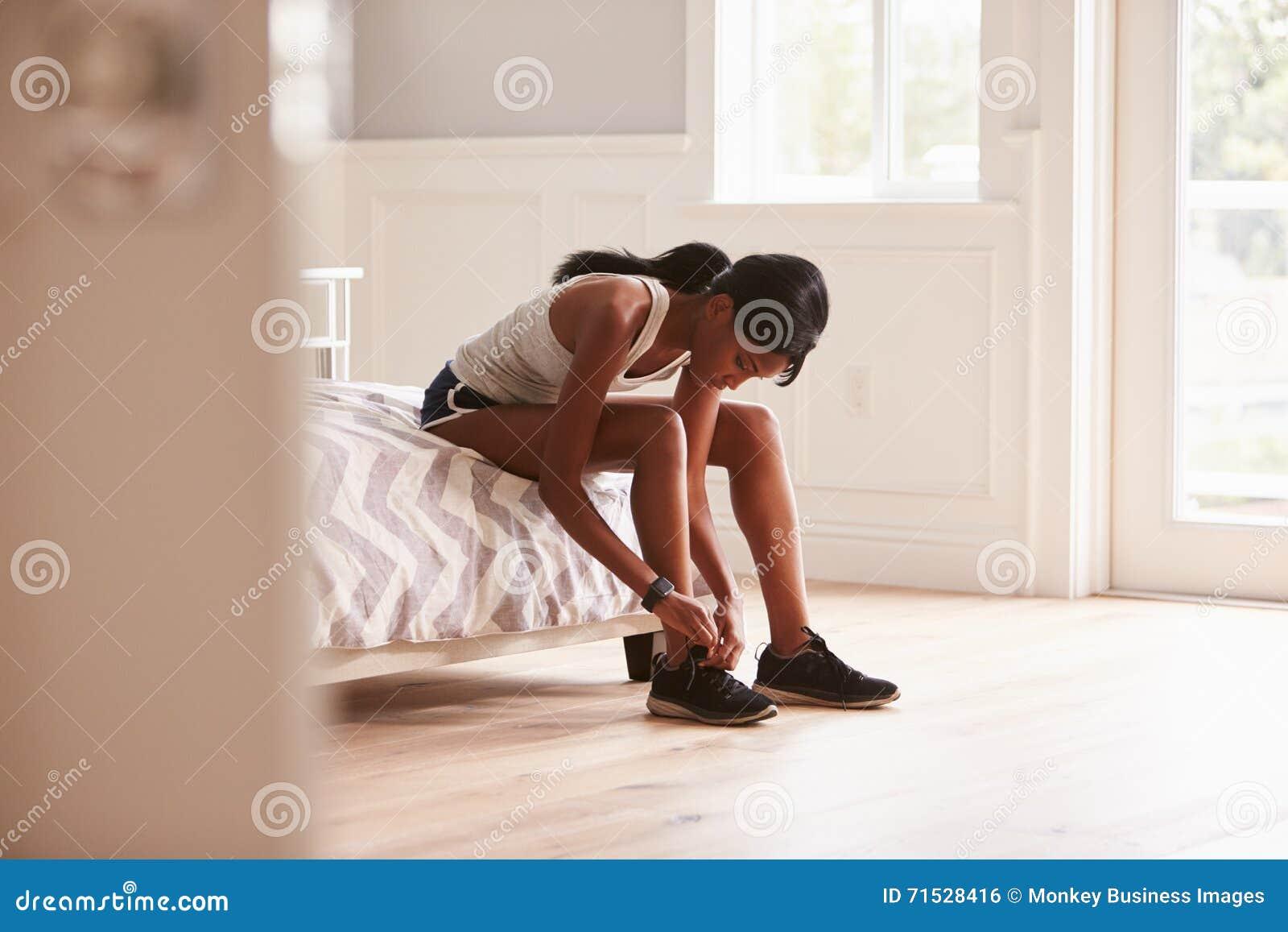Jeune femme de couleur prête pour s exercer attachant sa chaussure de sports