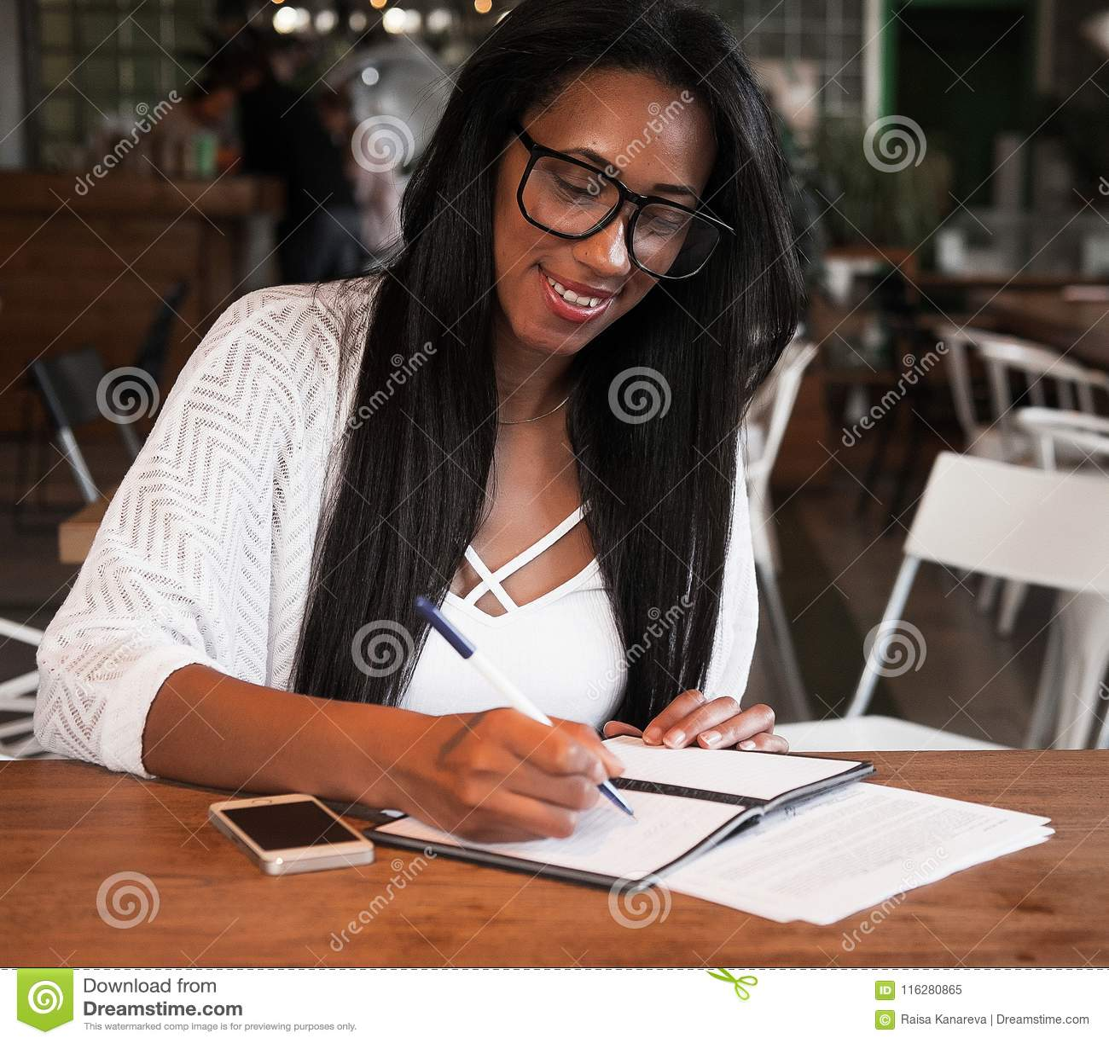 Jeune femme de couleur s asseyant au café et écrivant des notes, concept de mode de vie