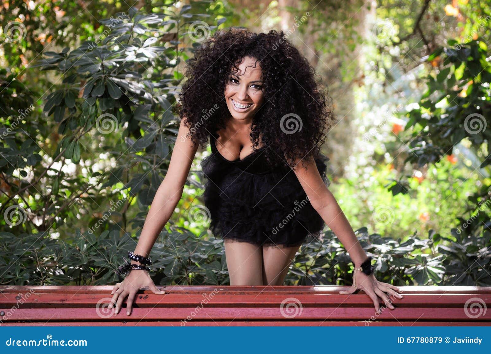 Jeune femme de couleur souriant avec des supports