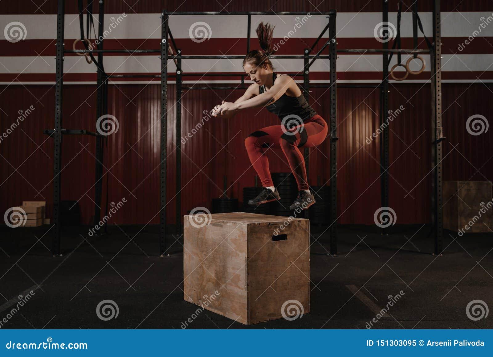 Jeune femme de crossfit faisant la boîte sautant au gymnase