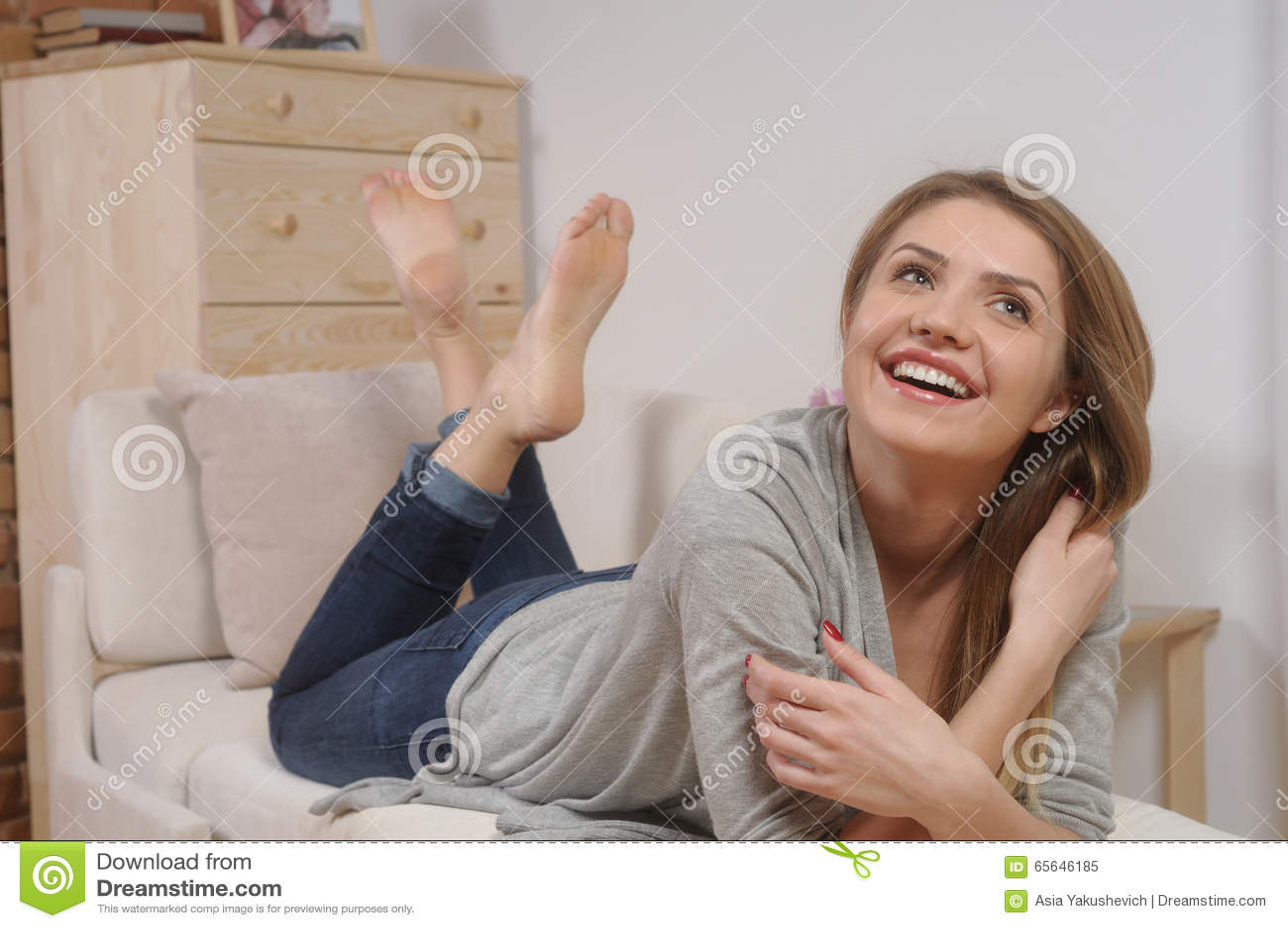 Jeune femme de sourire attirante se reposant sur le sofa à la maison