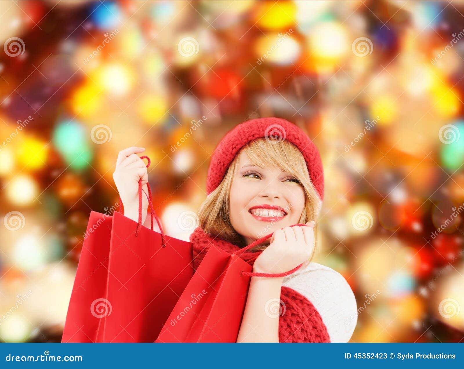 Jeune femme de sourire avec des sacs à provisions