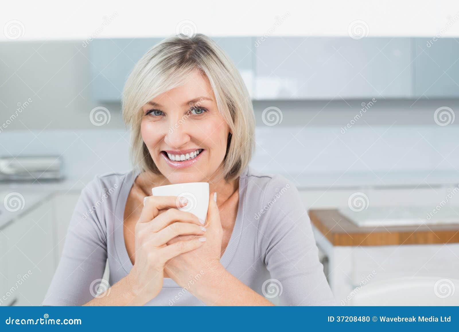 Jeune femme de sourire avec la tasse de café dans la cuisine à la maison