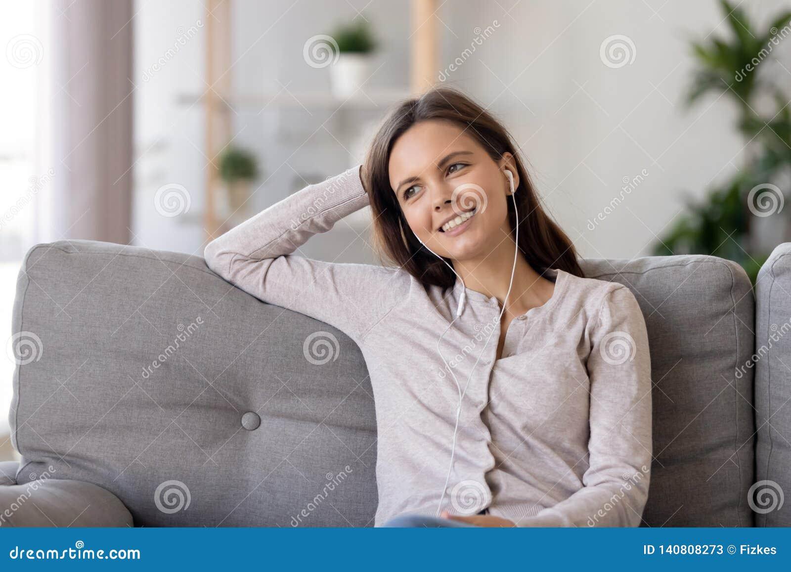 Jeune femme de sourire dans des écouteurs, écoutant la musique préférée