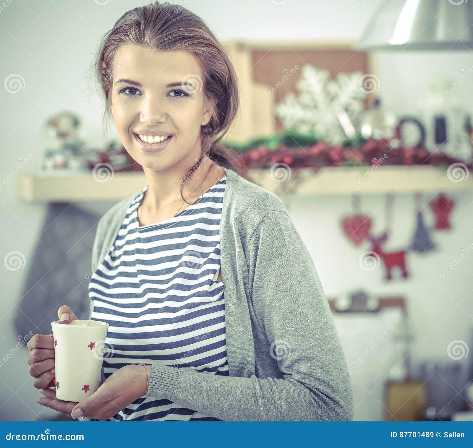 Jeune femme de sourire dans la cuisine, d isolement sur le fond de Noël