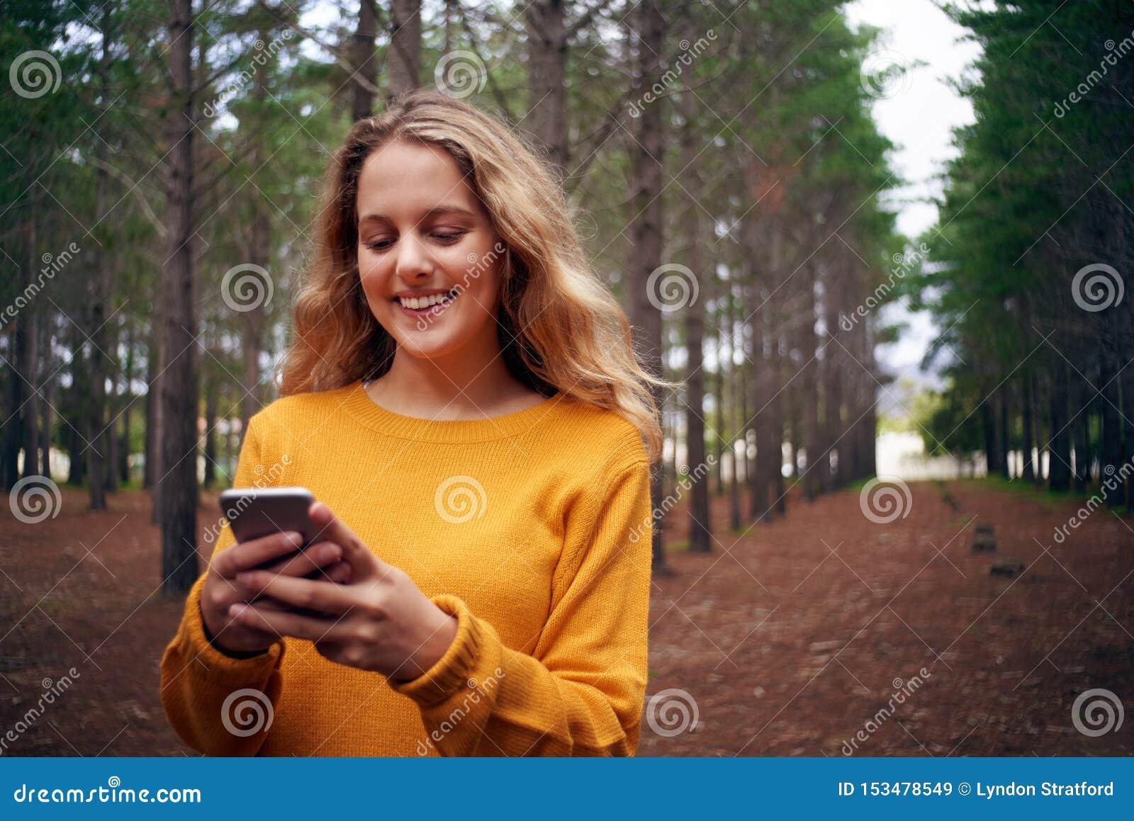 Jeune femme de sourire dans la forêt utilisant le téléphone portable