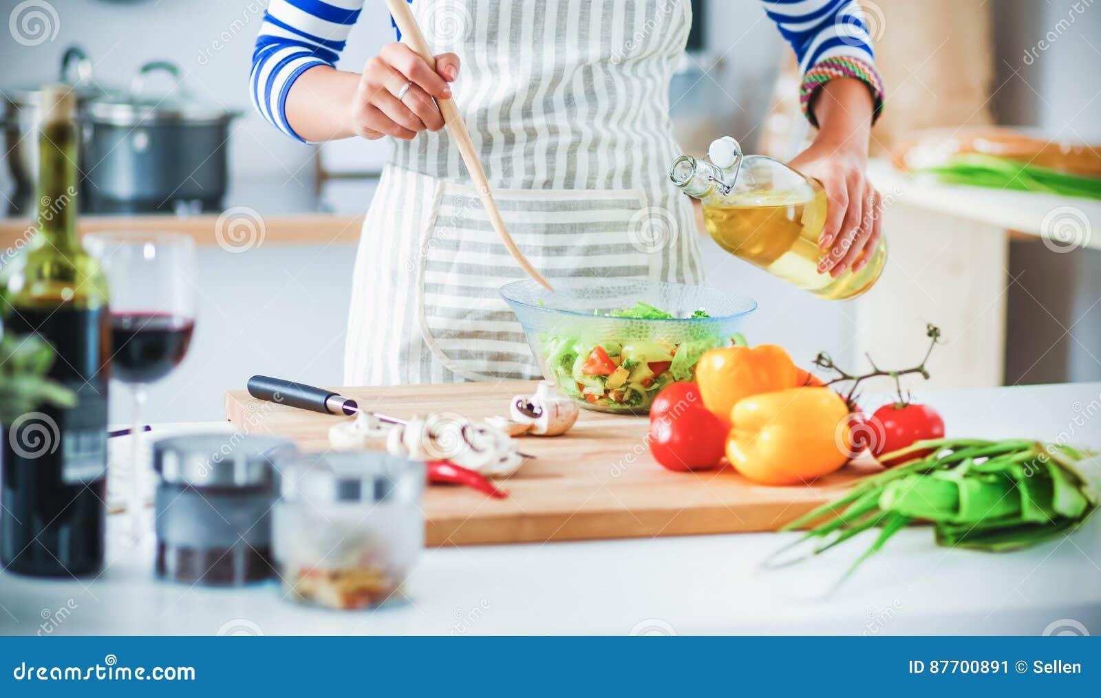 Jeune femme de sourire mélangeant la salade fraîche