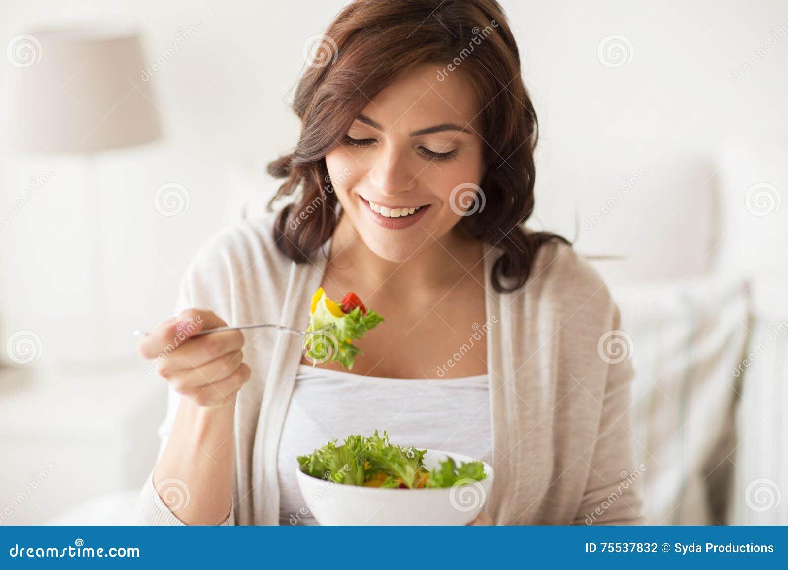 Jeune femme de sourire mangeant de la salade à la maison