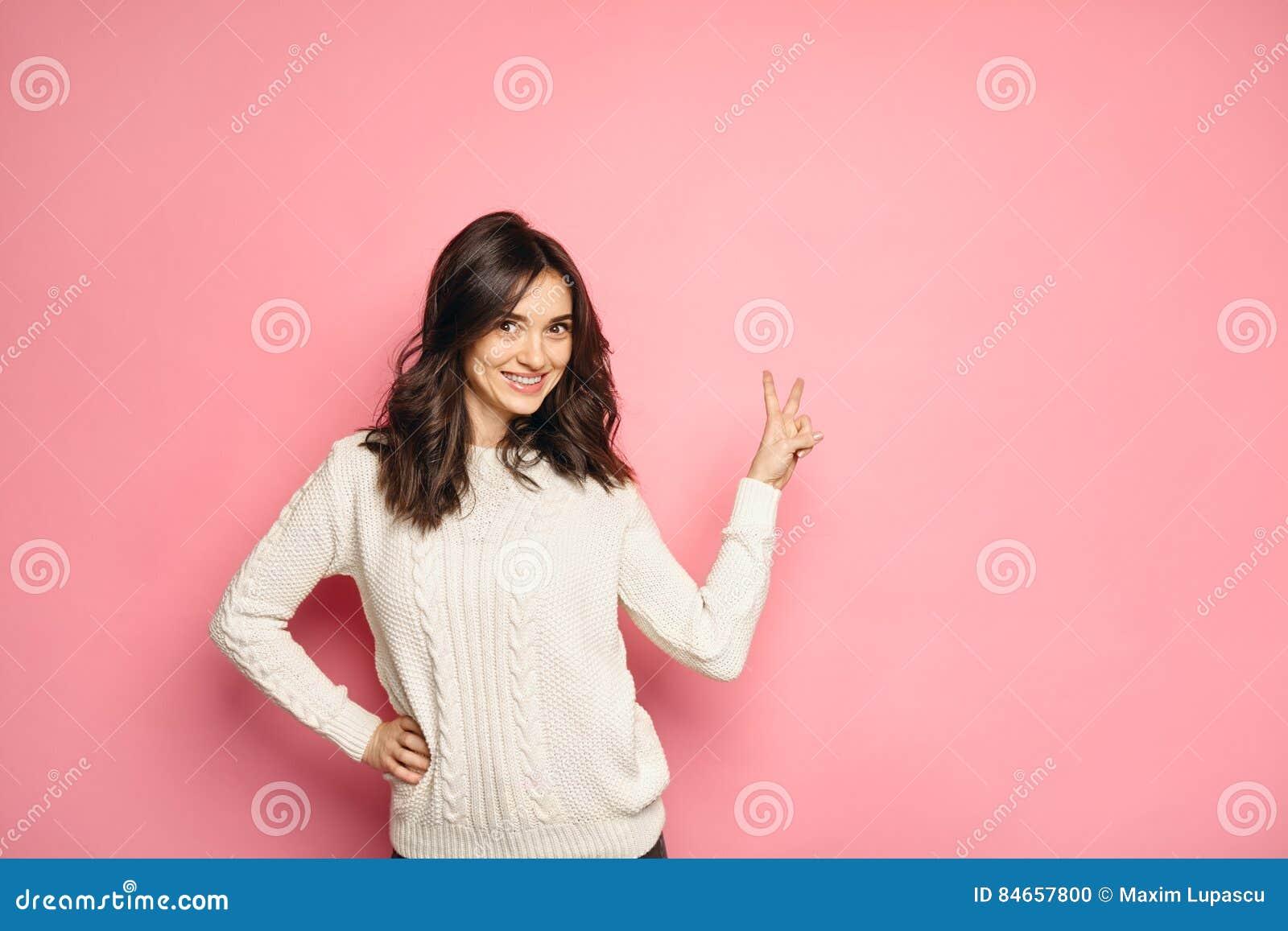 Jeune femme de sourire montrant le signe de main de paix