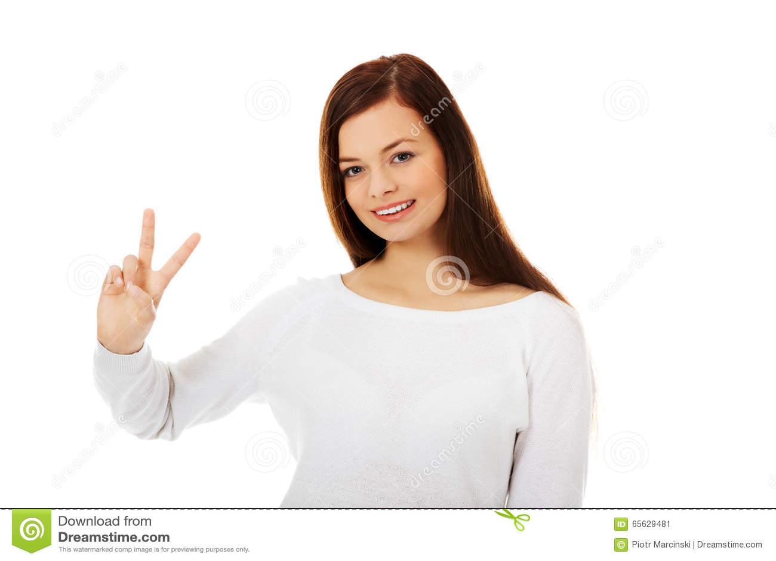 Jeune femme de sourire montrant le signe de victoire