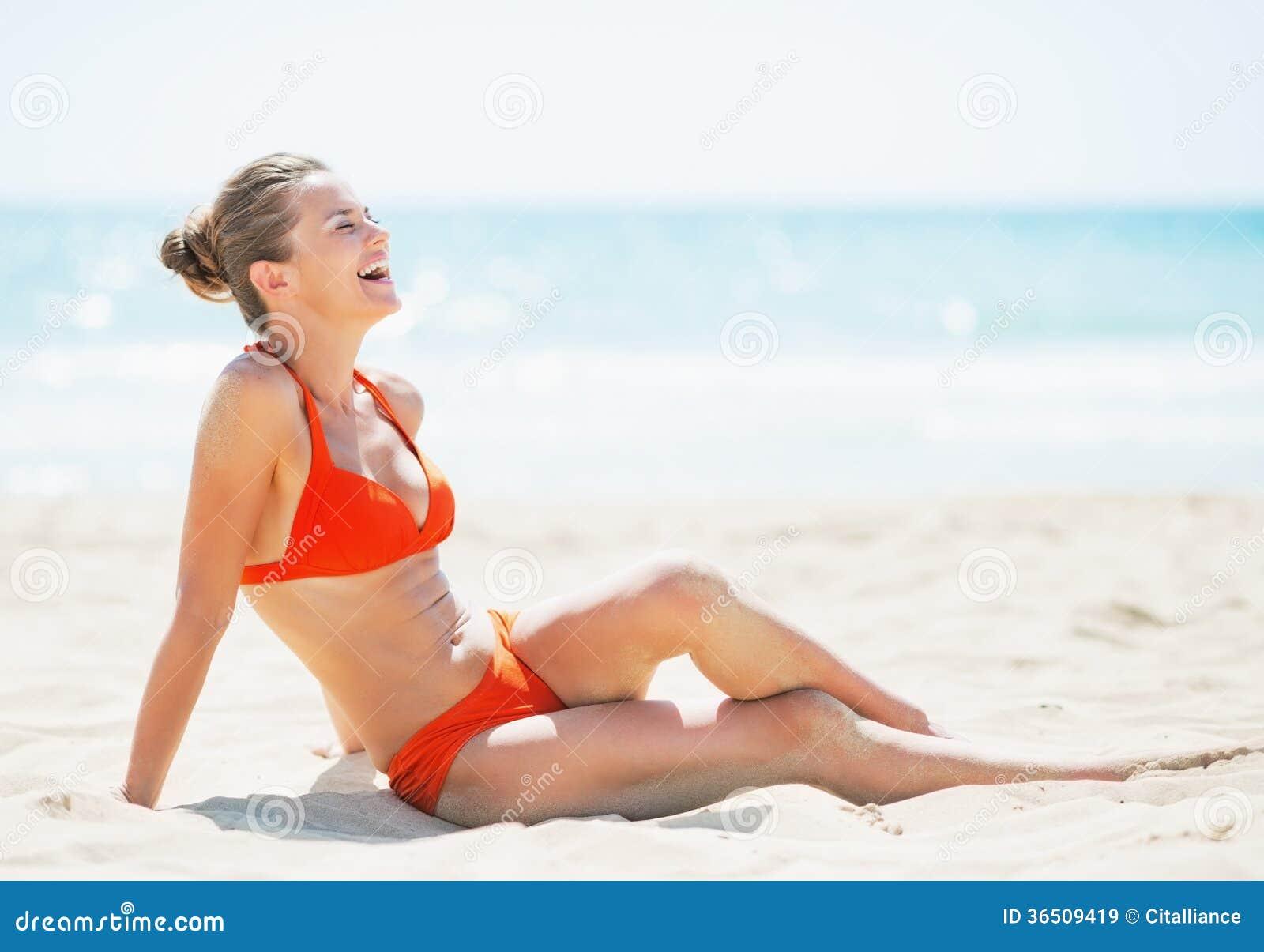 Jeune femme de sourire s étendant sur la plage