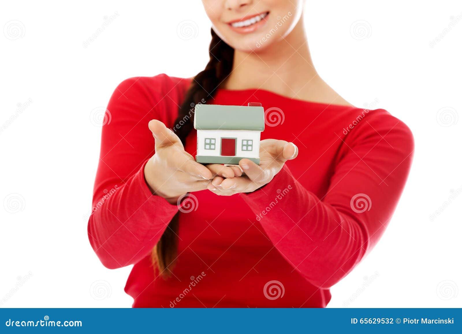 Jeune femme de sourire tenant le modèle de maison