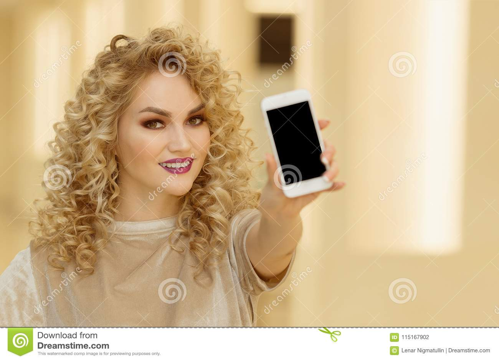 Jeune femme de sourire tenant le téléphone portable dans le mail
