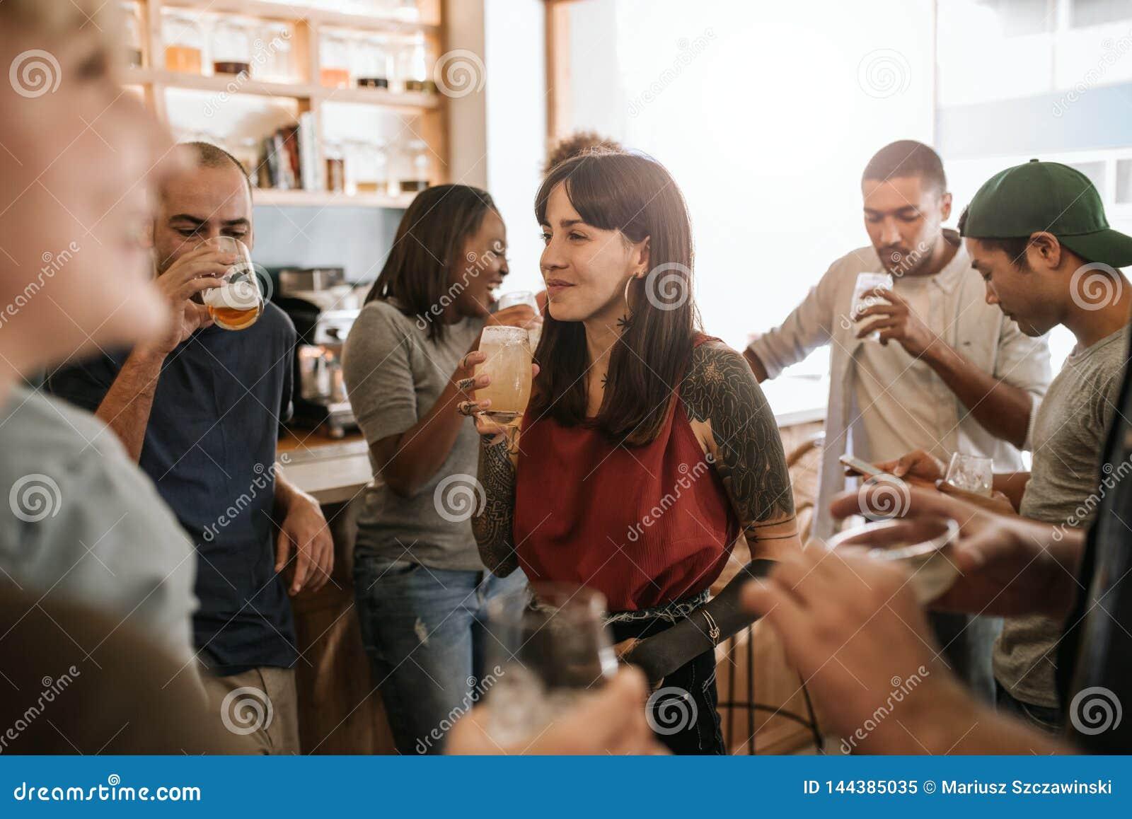 Jeune femme de sourire traînant avec des amis dans une barre