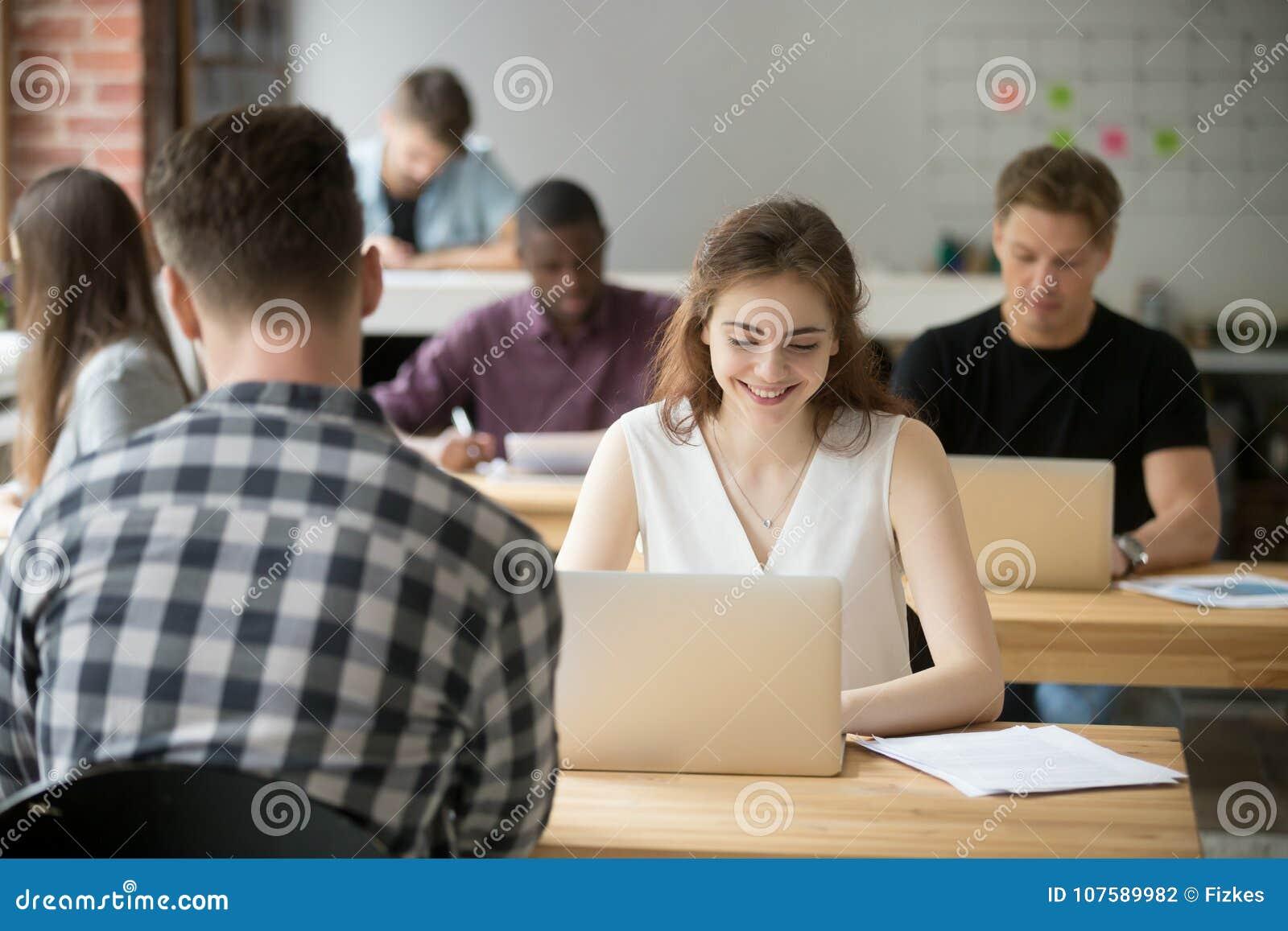 Jeune femme de sourire travaillant sur l ordinateur portable dans les bureaux coworking