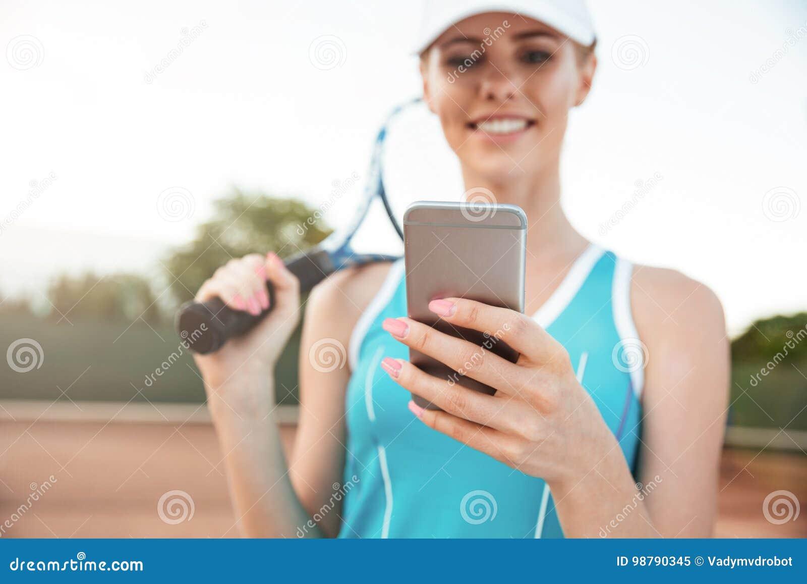 Jeune femme de tennis avec le téléphone