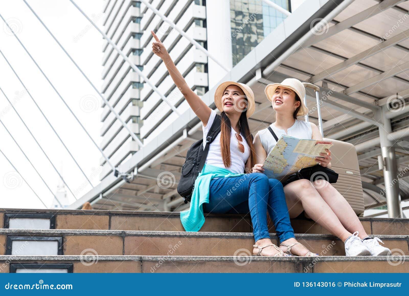 Jeune femme de touristes asiatique se dirigeant dans la distance tandis que son ami regardant avec les visages de sourire