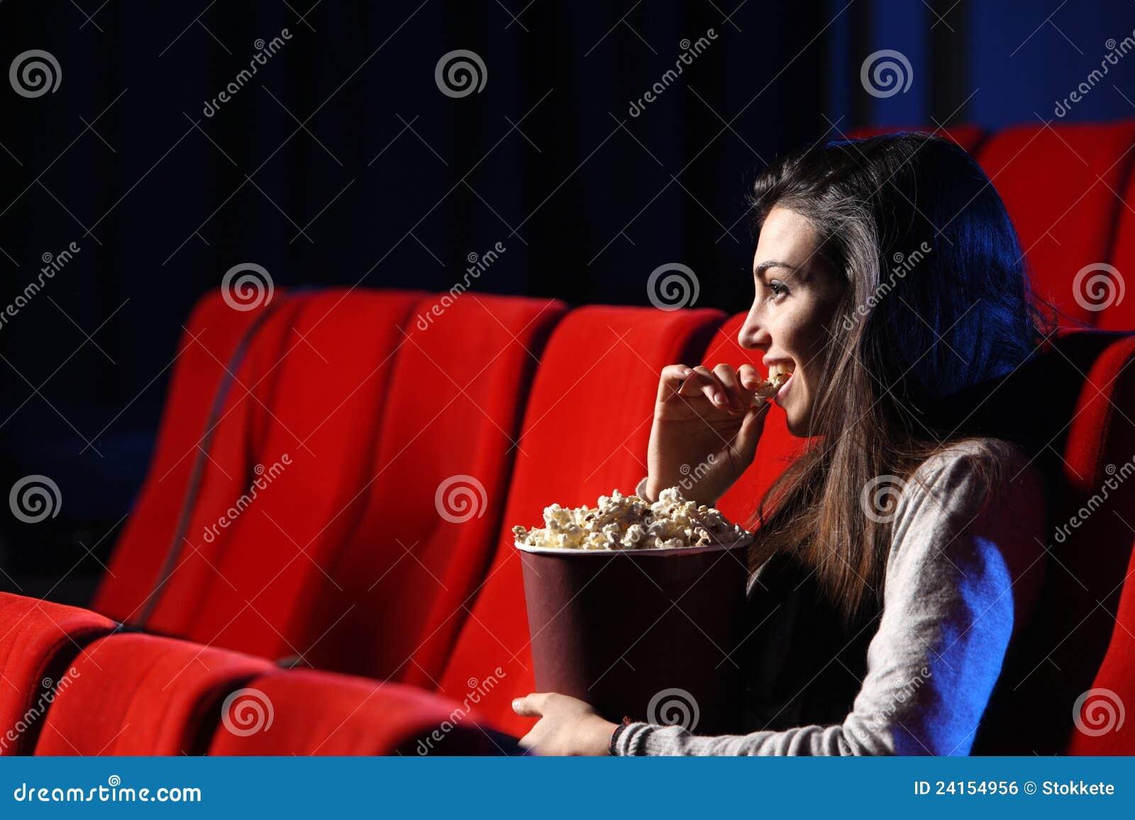 Jeune femme, elle mange du maïs éclaté et sourit