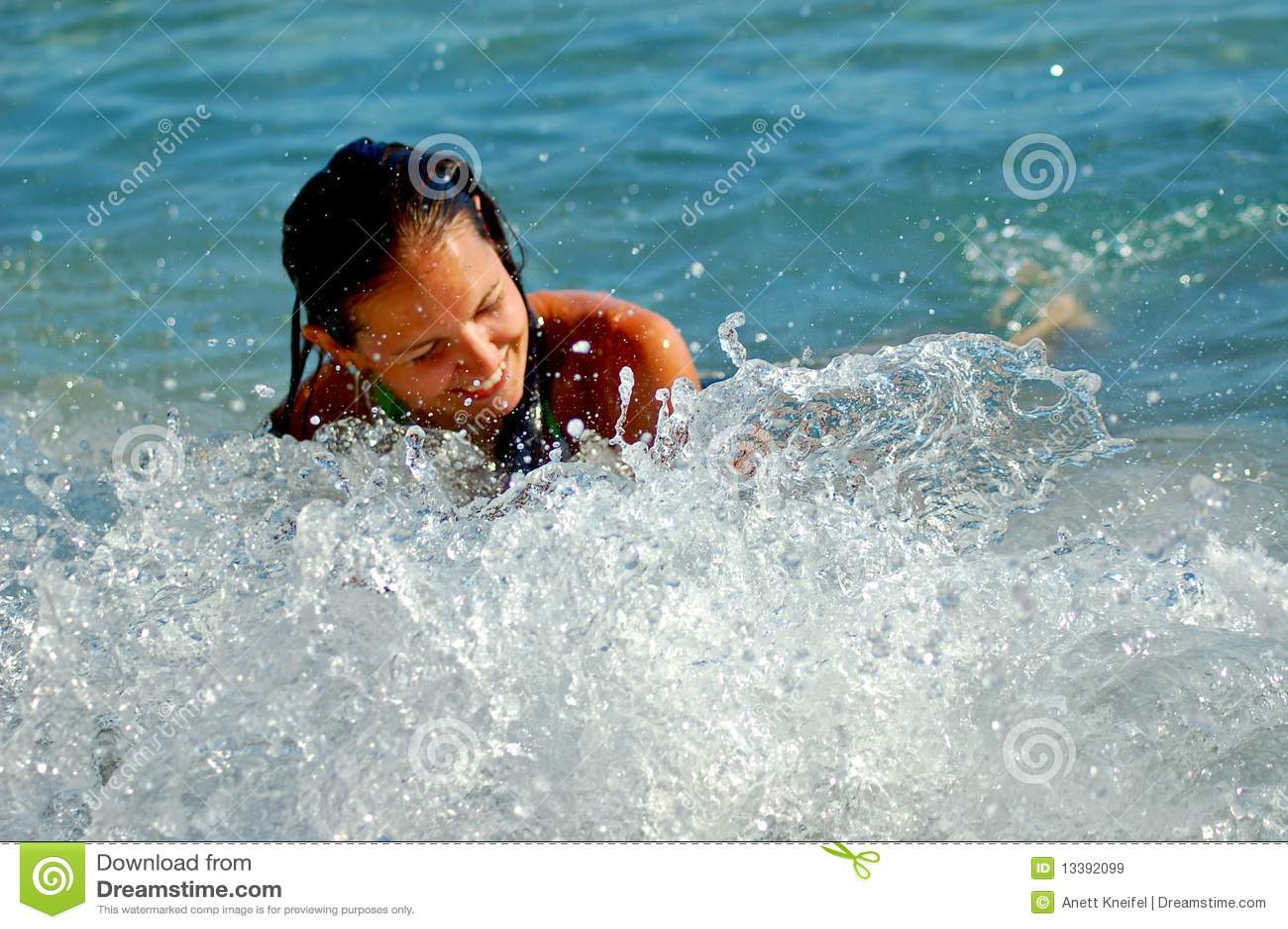 Jeune femme en éclaboussant des ondes