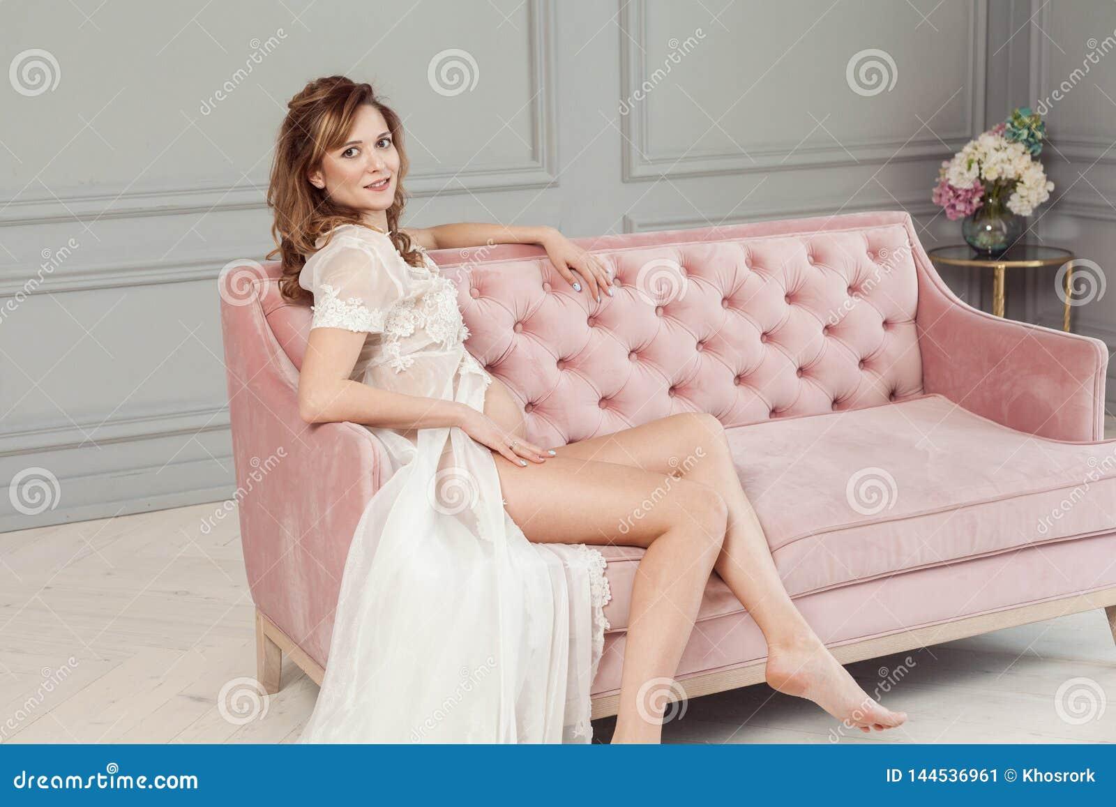 Jeune femme enceinte dans le peignoir blanc de robe se reposant sur le sofa rose, montrant son ventre nu et belles jambes, regard