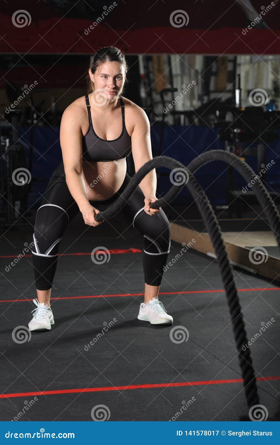 Jeune femme enceinte faisant des exercices durs de séance d entraînement avec les cordes noires
