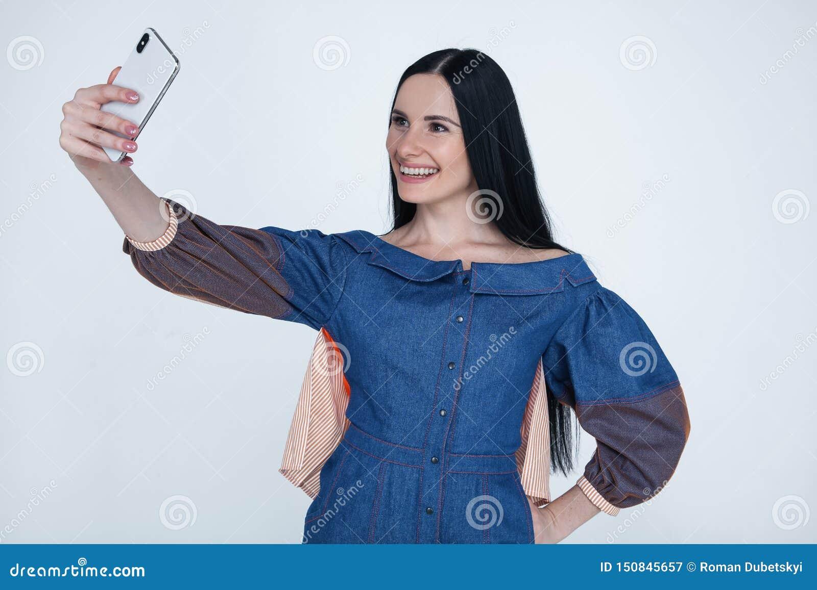 Jeune femme enthousiaste de brune faisant le selfie utilisant le t?l?phone intelligent Fille d étudiant avec de longs cheveux dan
