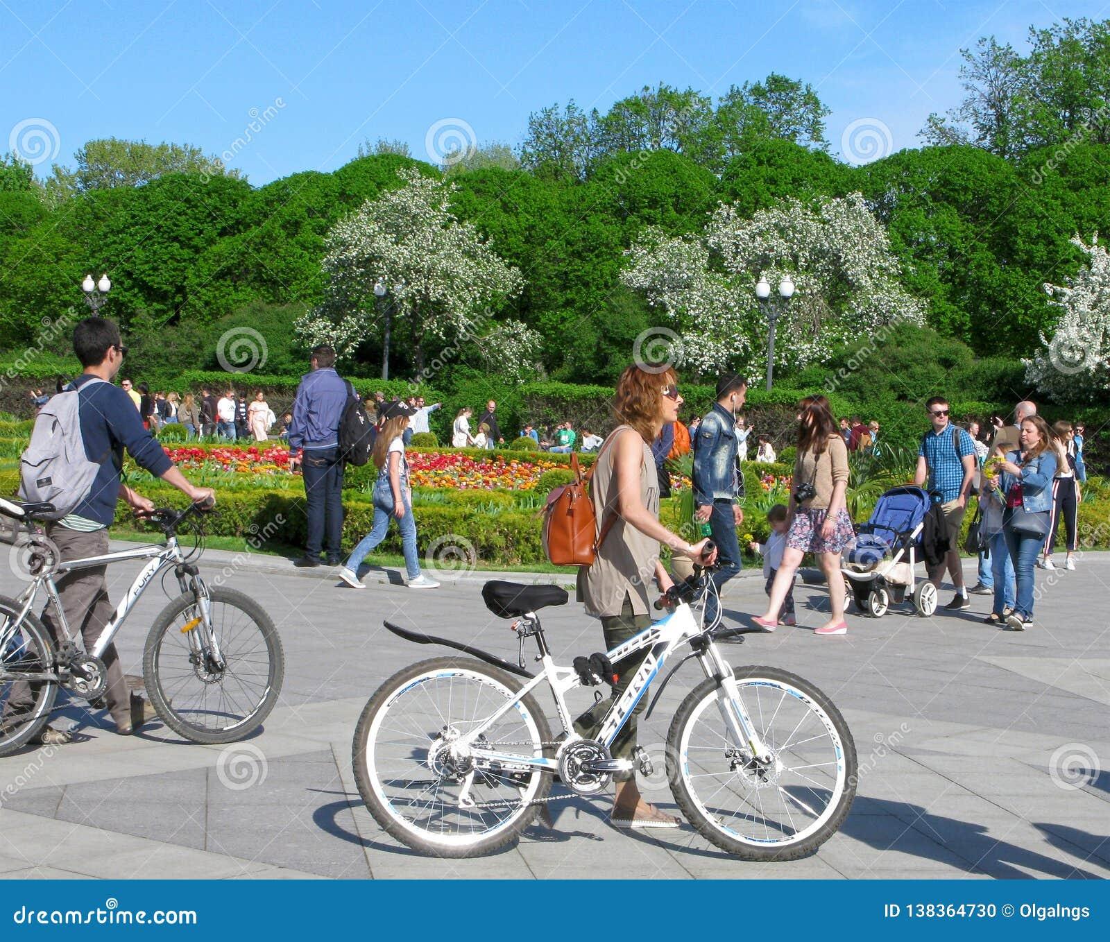 Jeune femme et homme avec des bicyclettes en parc de ville
