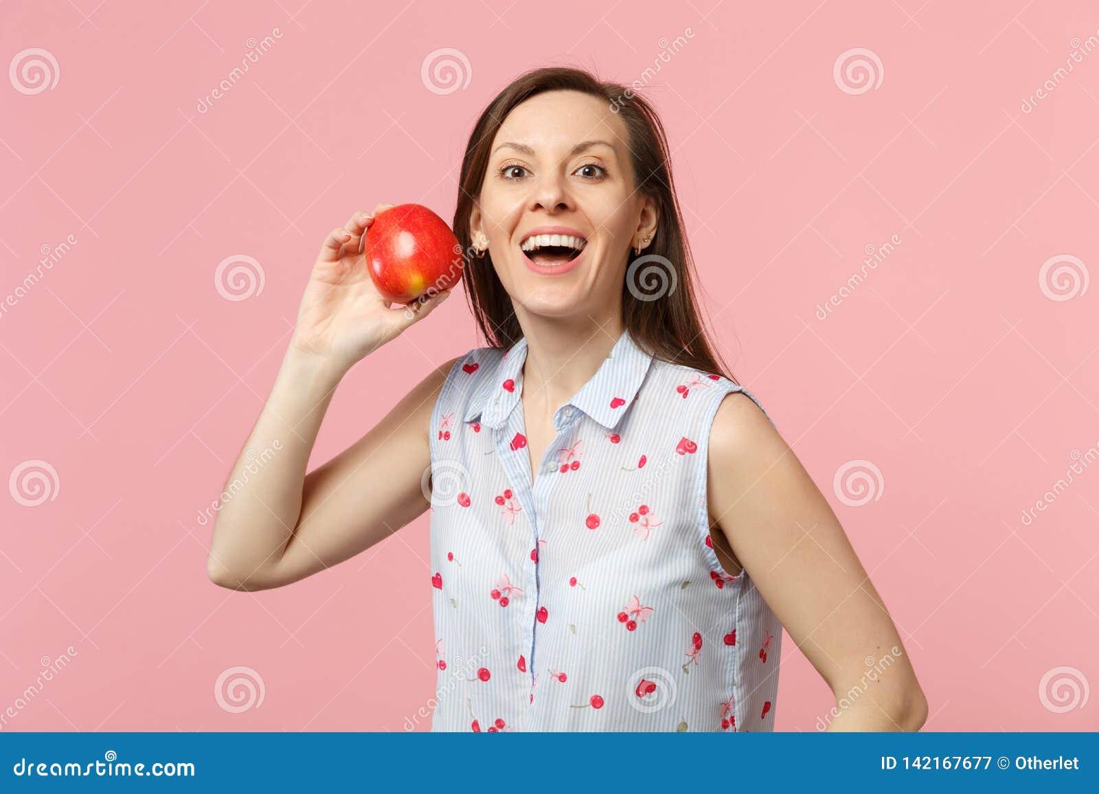 Jeune Femme Excitée Dans Des Vêtements D été Jugeant Le Fruit Rouge Mûr Frais De Pomme D Isolement Sur Le Fond En Pastel Rose De Image Stock Image Du Mûr Rose 142167677
