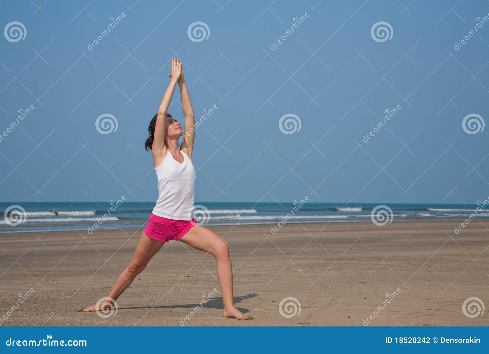 Jeune femme faisant le yoga sur la plage