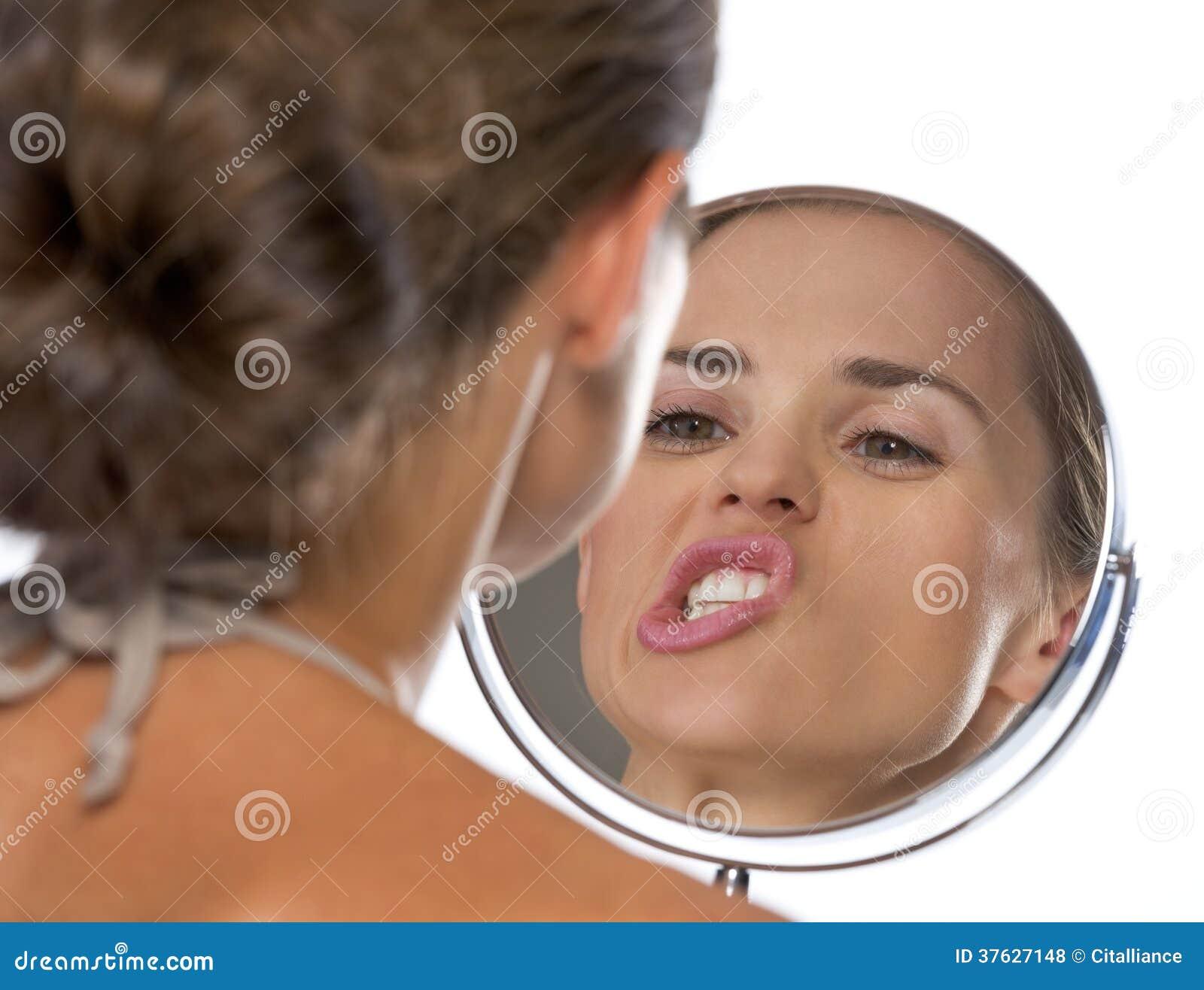 Jeune femme faisant les visages dr les tout en regardant for Regard dans le miroir