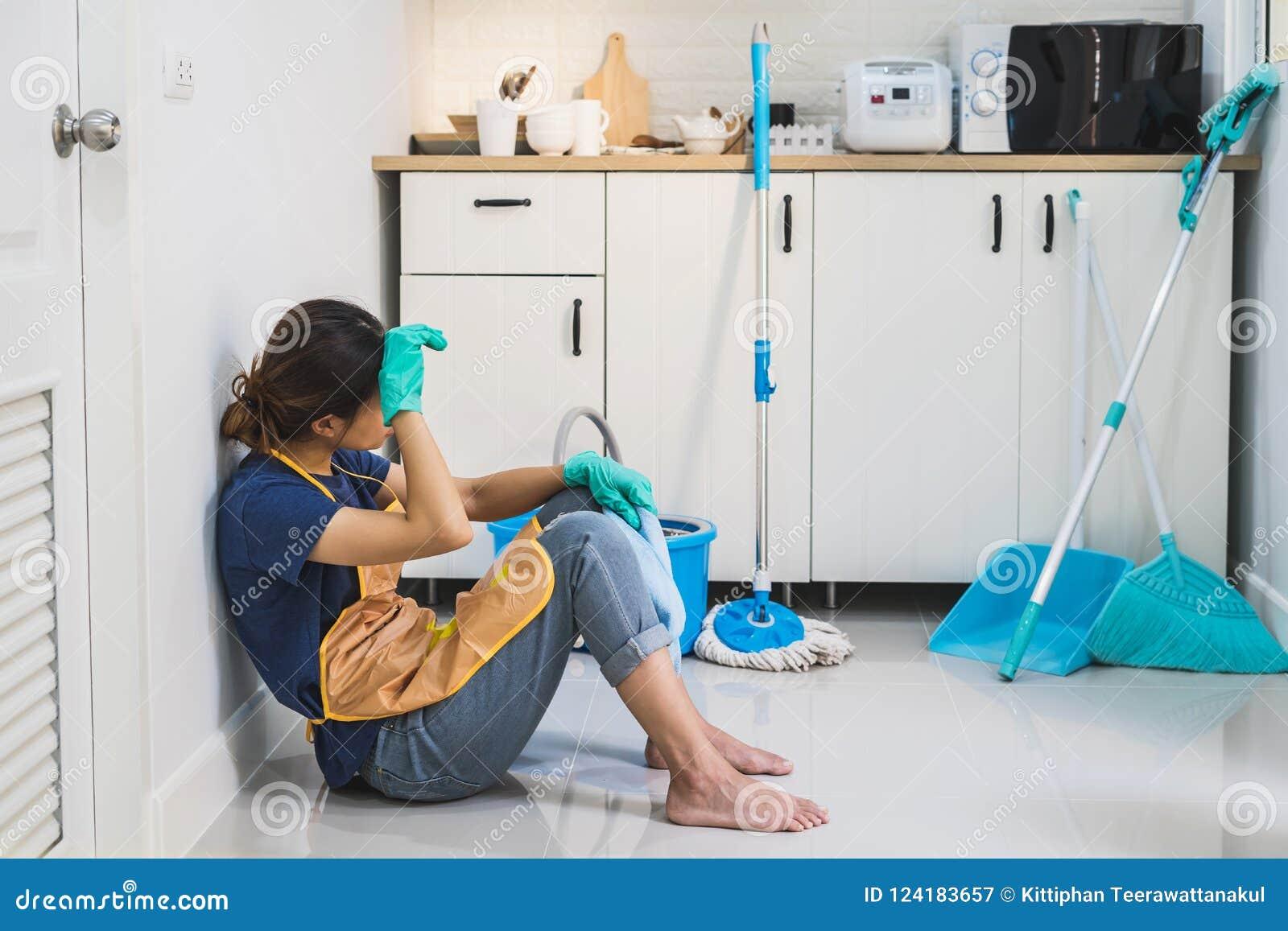 Jeune femme fatiguée s asseyant sur le plancher de cuisine