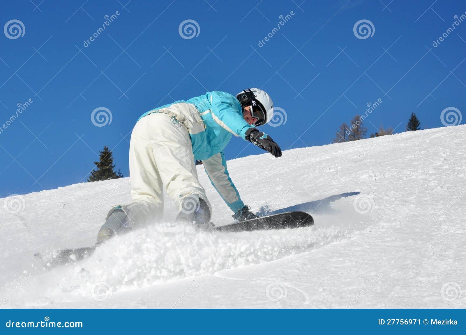 Jeune femme freinant sur le snowboard