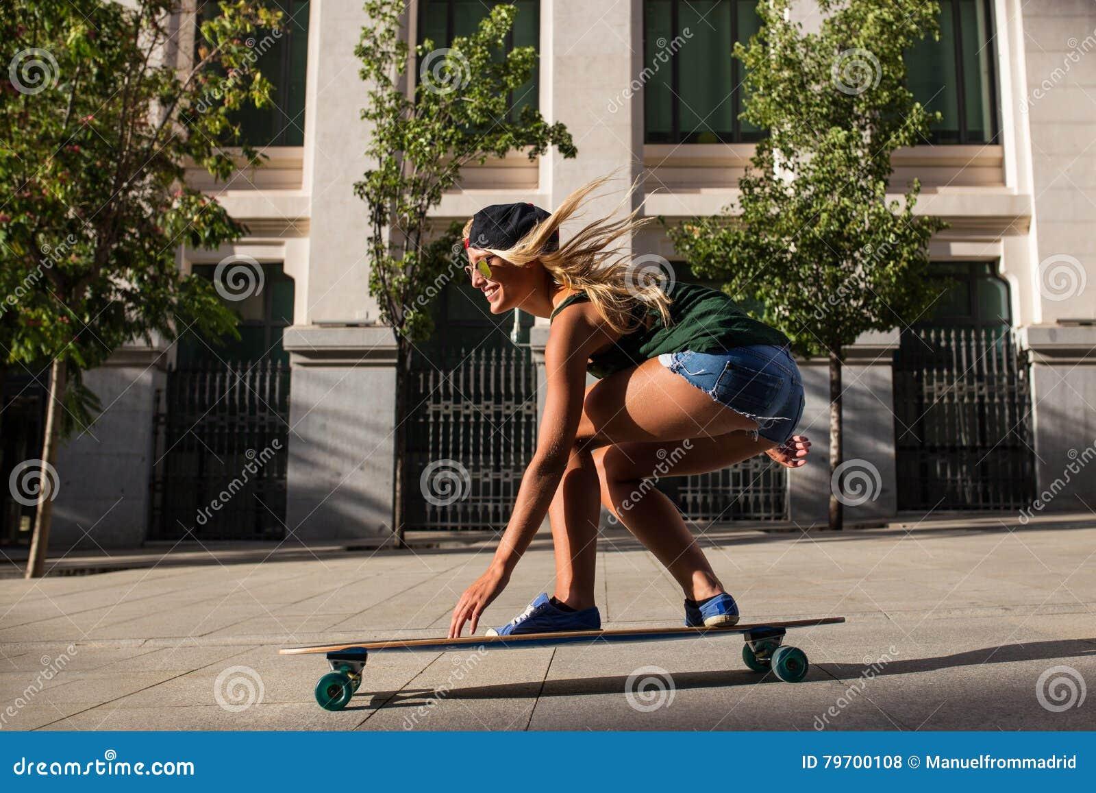 Jeune femme gaie attirante avec une planche à roulettes