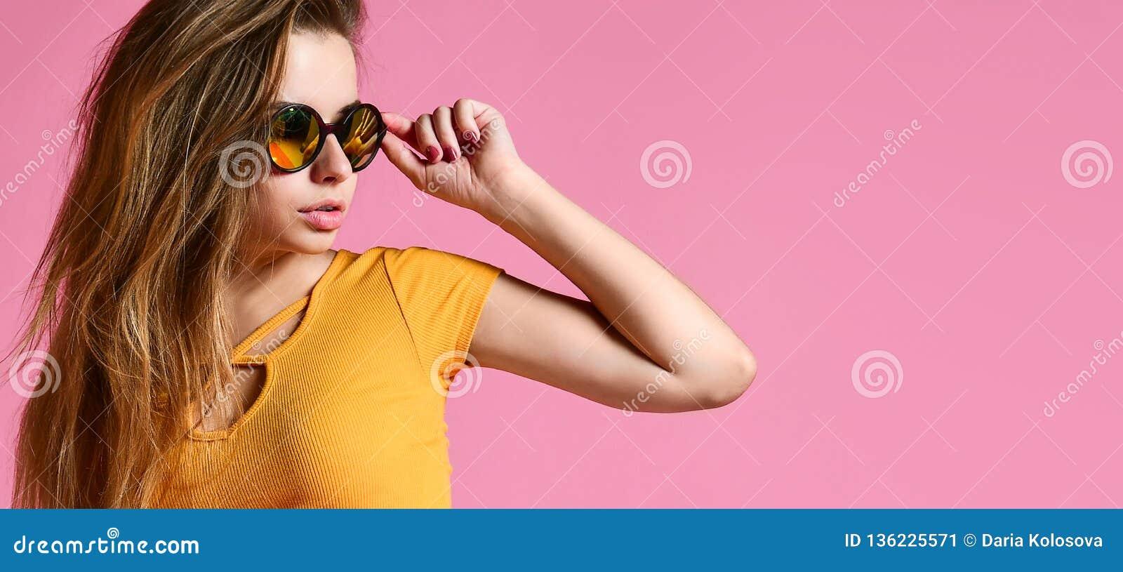 Jeune femme gaie dans des lunettes de soleil sur le fond rose