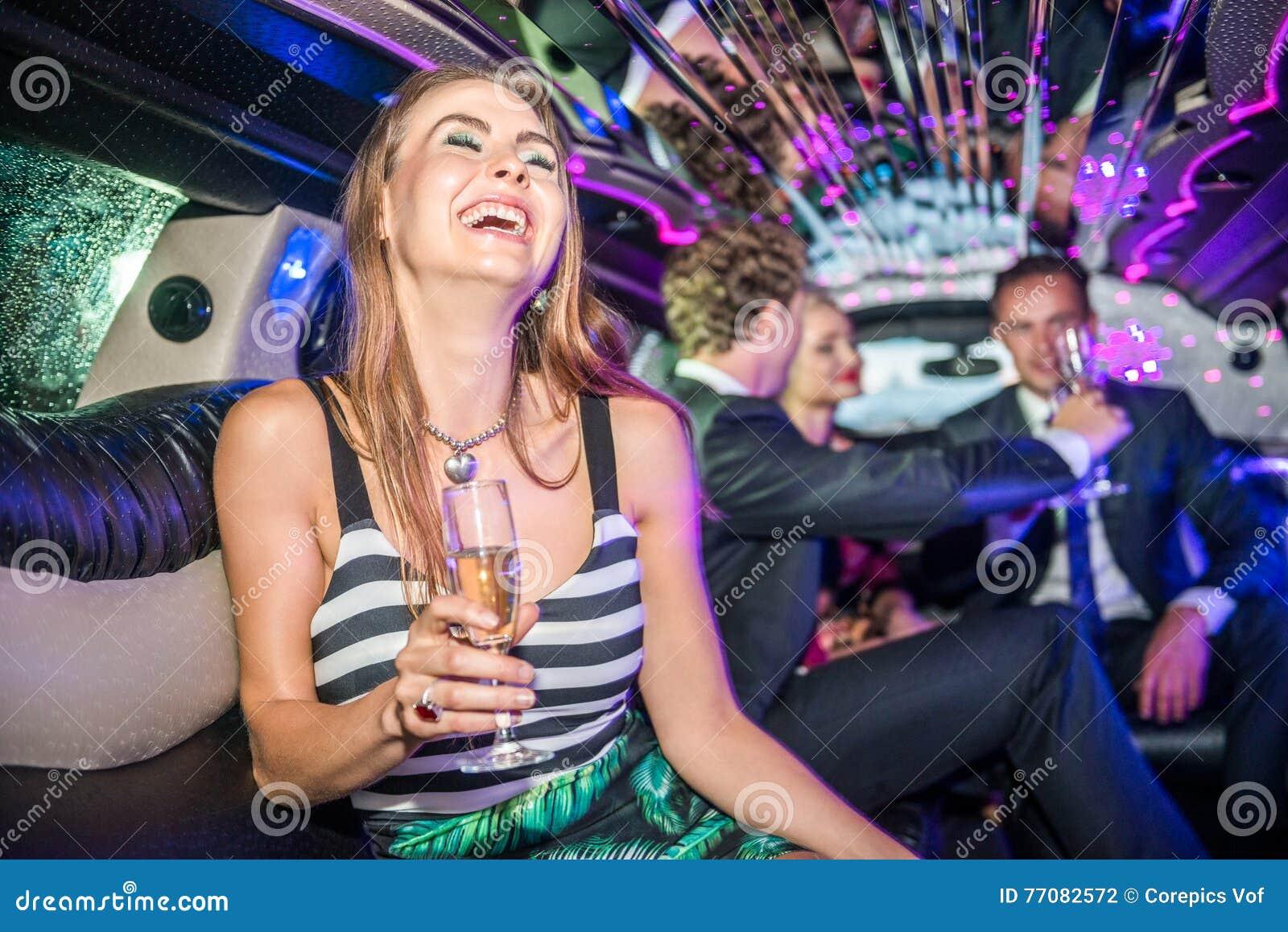 Jeune femme gaie tenant la cannelure de champagne tandis que célébrité d amis